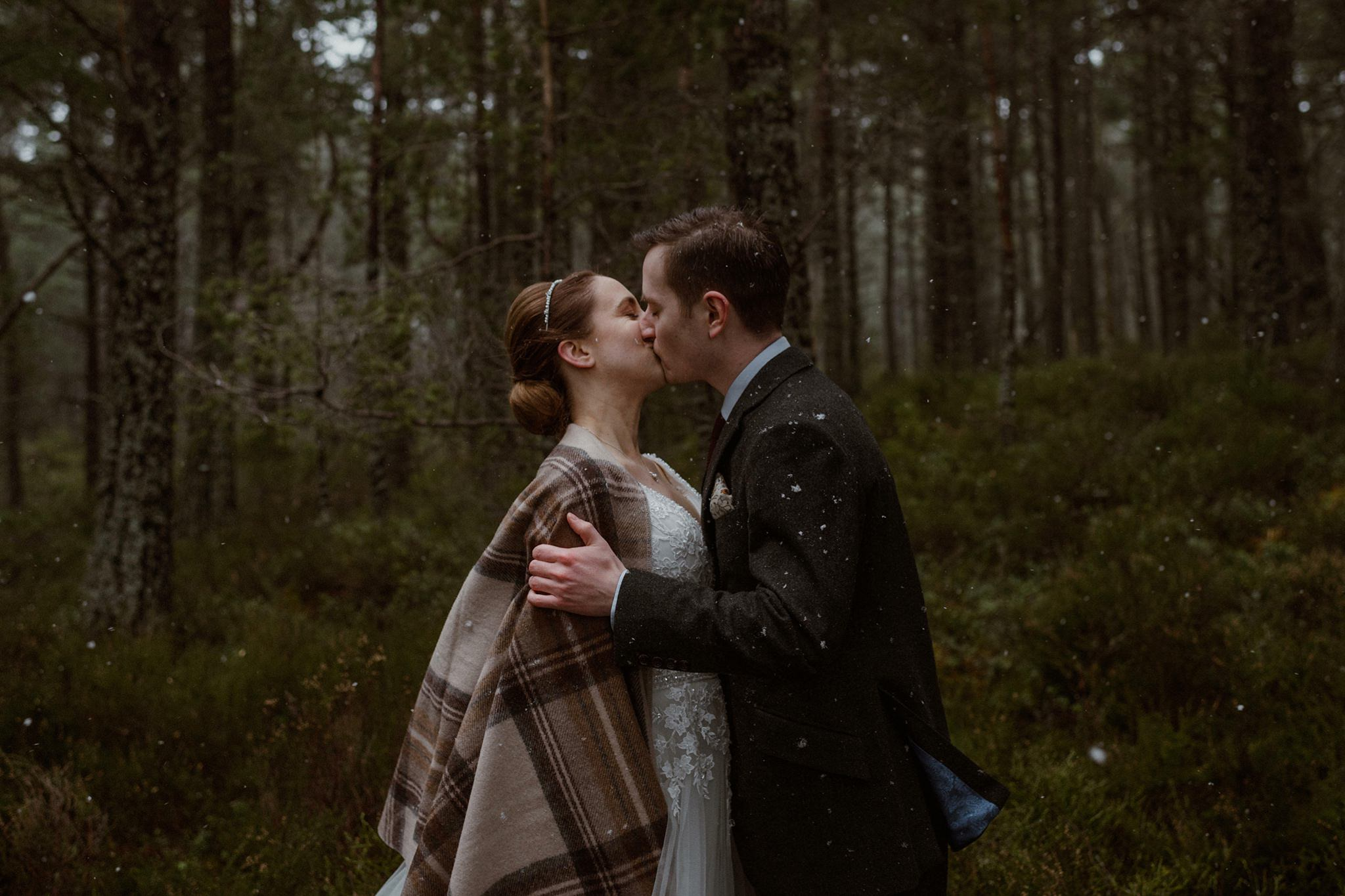 Just married in the snow Rothiemurchus forest Cairngorms Scotland