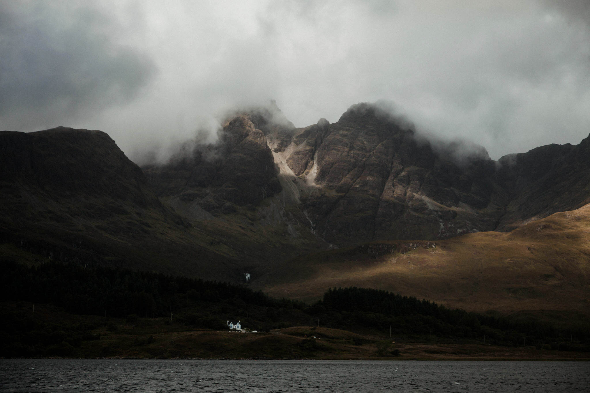 Isle of Skye elopement moody Scottish landscape featuring misty mountains a loch and white cottage