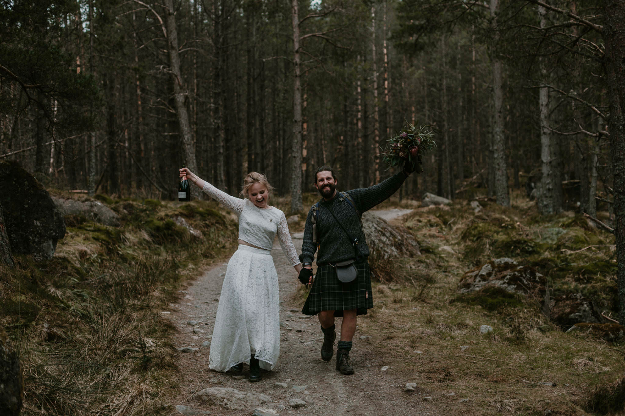 Scottish elopement couple walking through woods celebrating with champagne