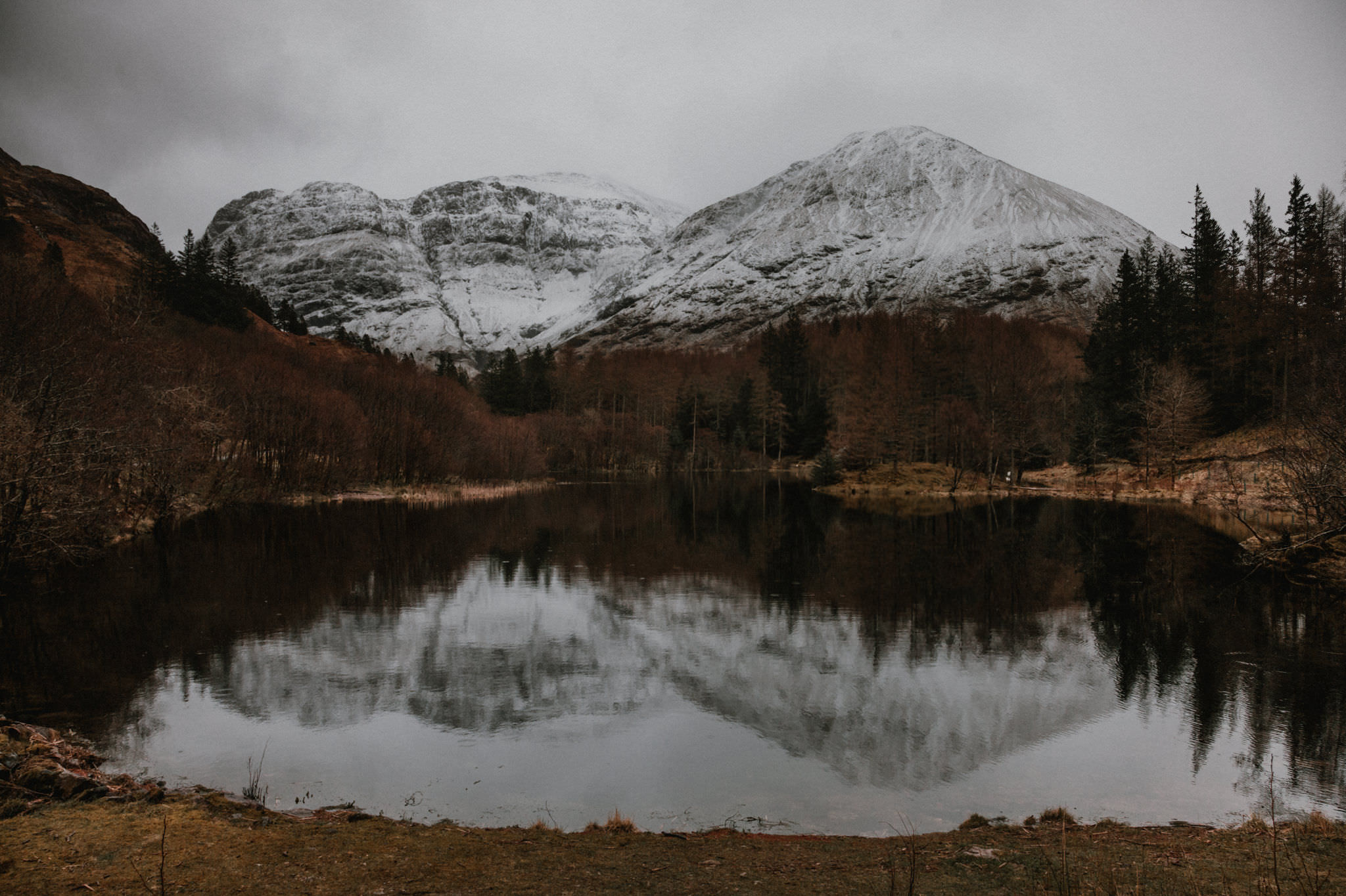 Glencoe elopement still loch with reflections of snow covered mountians