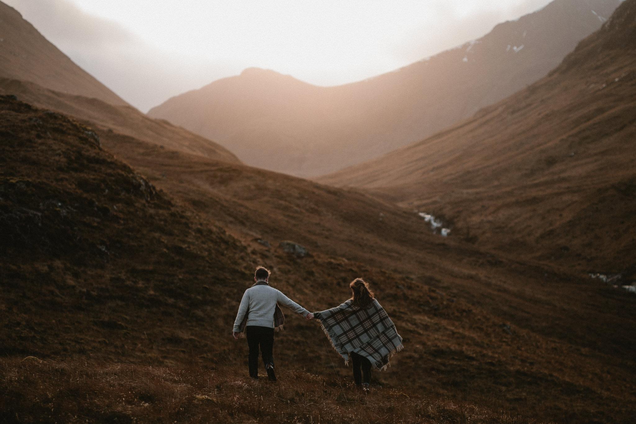 Glencoe couples shoot couple walking through mountains at sunset