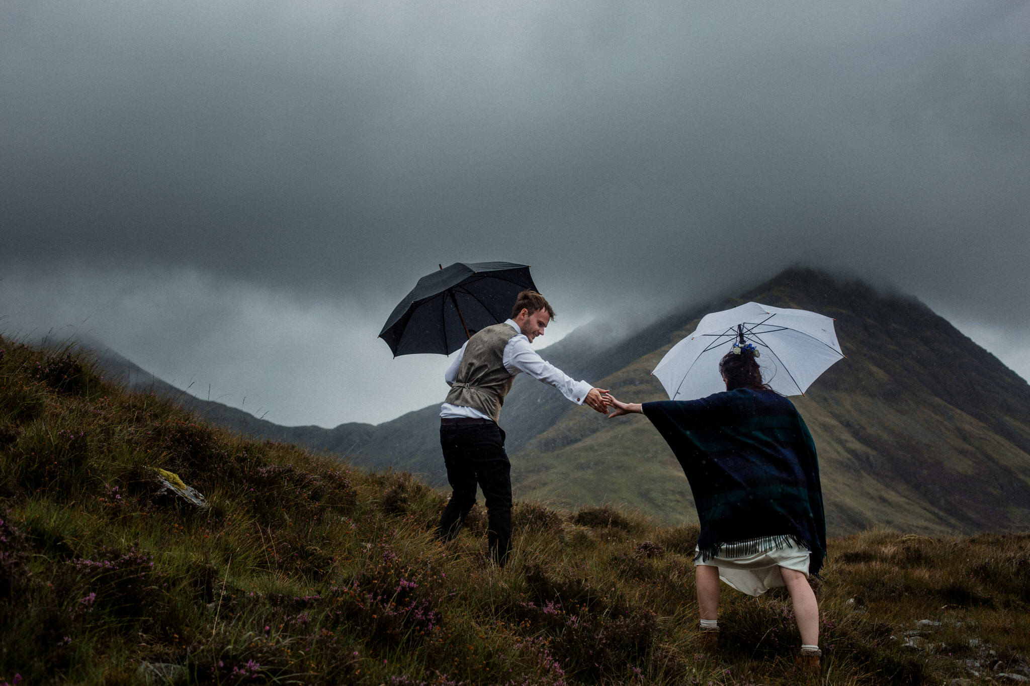 Isle of Skye elopement couple battle against the weather on hillside holding umbrellas
