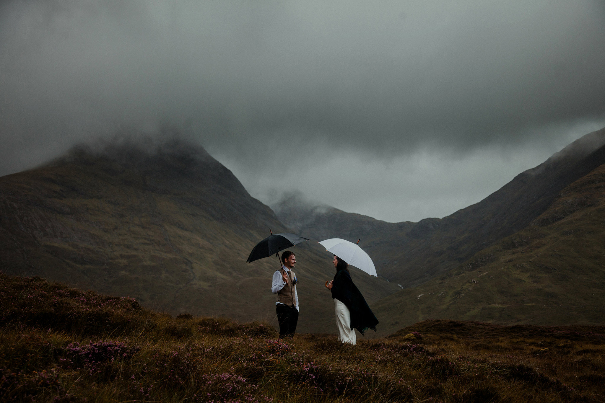 Isle of Skye elopement couple standing amidst the mountains in rain holding umbrellas