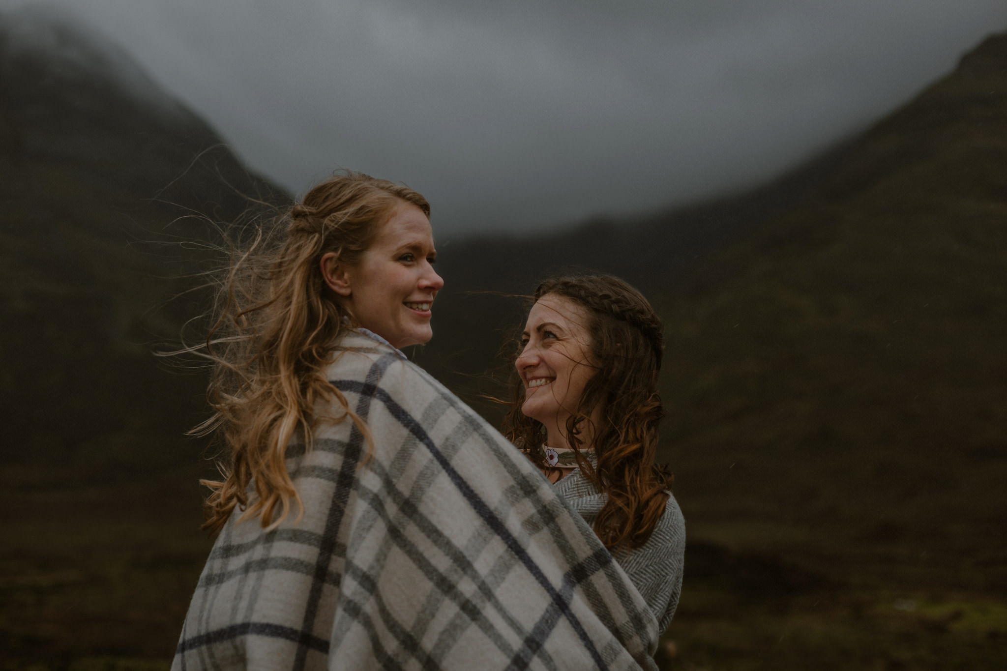 Isle of Skye elopement couple on hillside with hair blowing in the wind