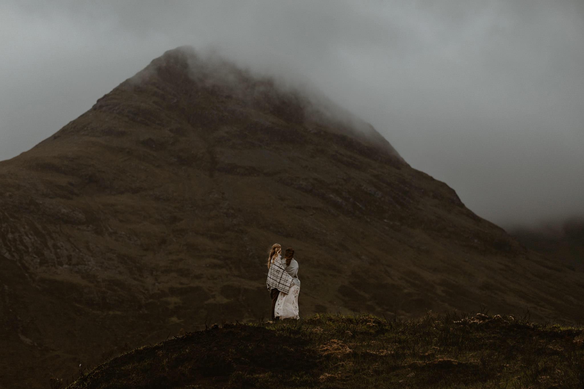 Isle of Skye elopement couple under vast misty mountain