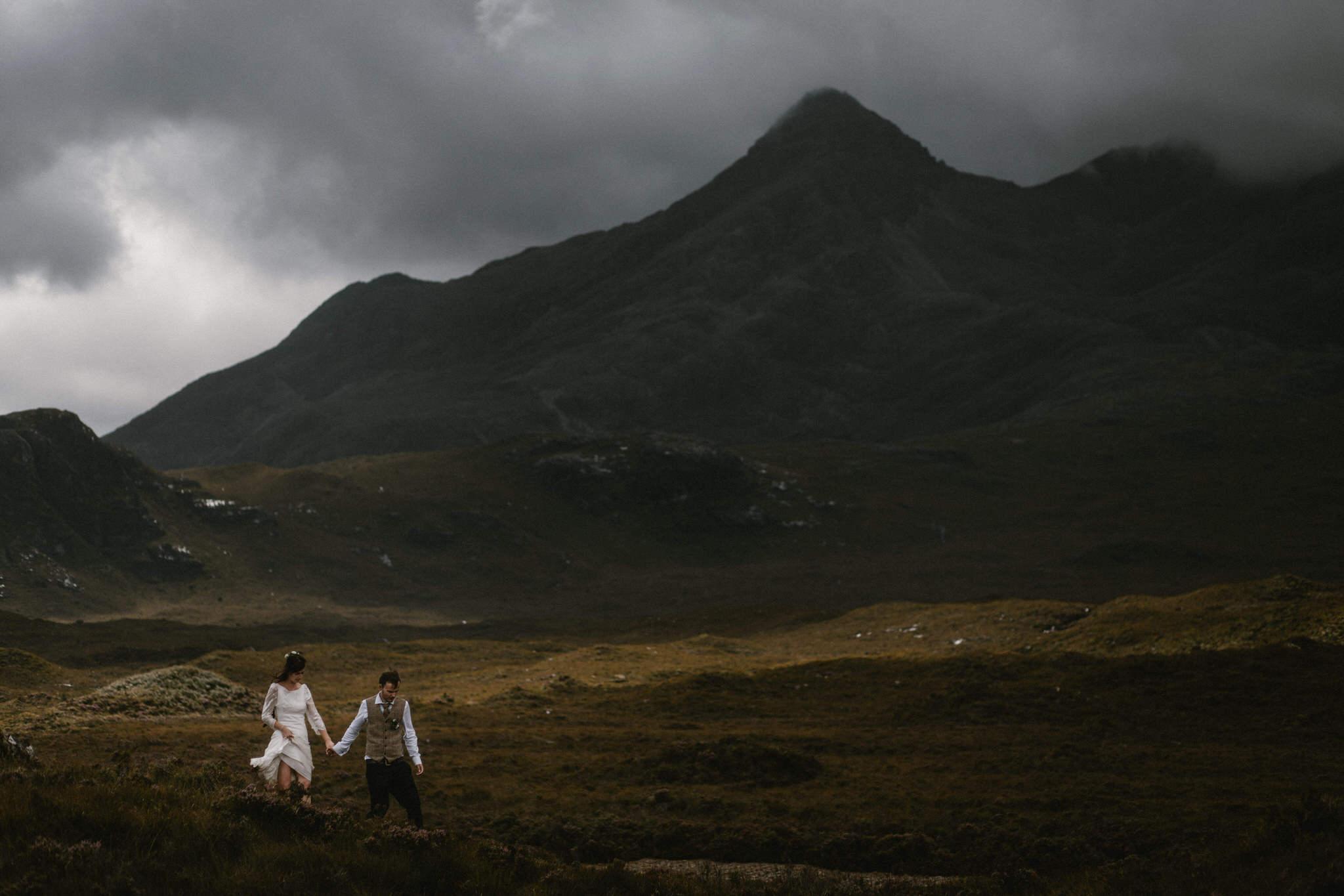 Isle of Skye elopement couple walk through moody mountain scenery