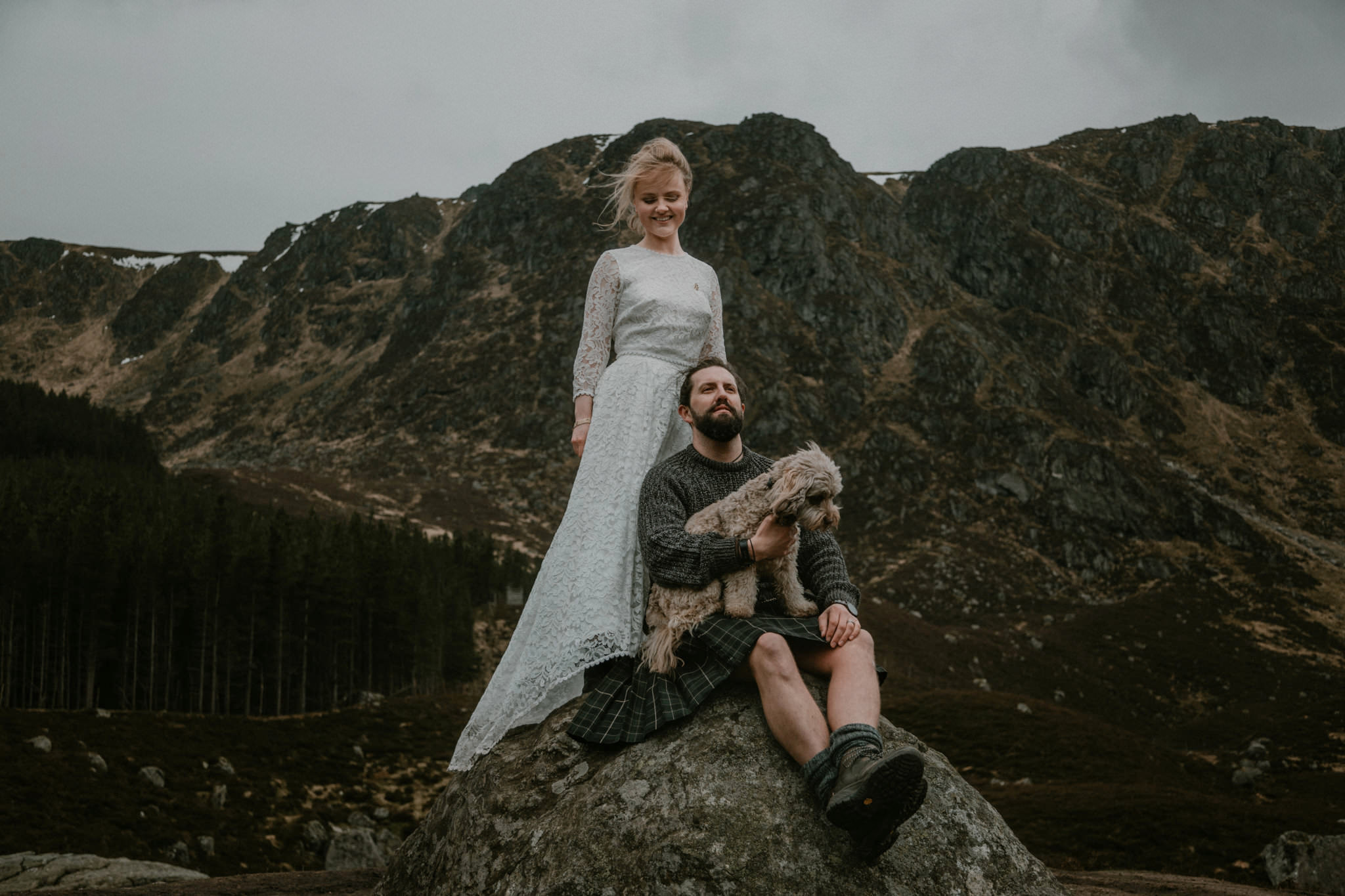 Scotland elopement couple post on rock with dog