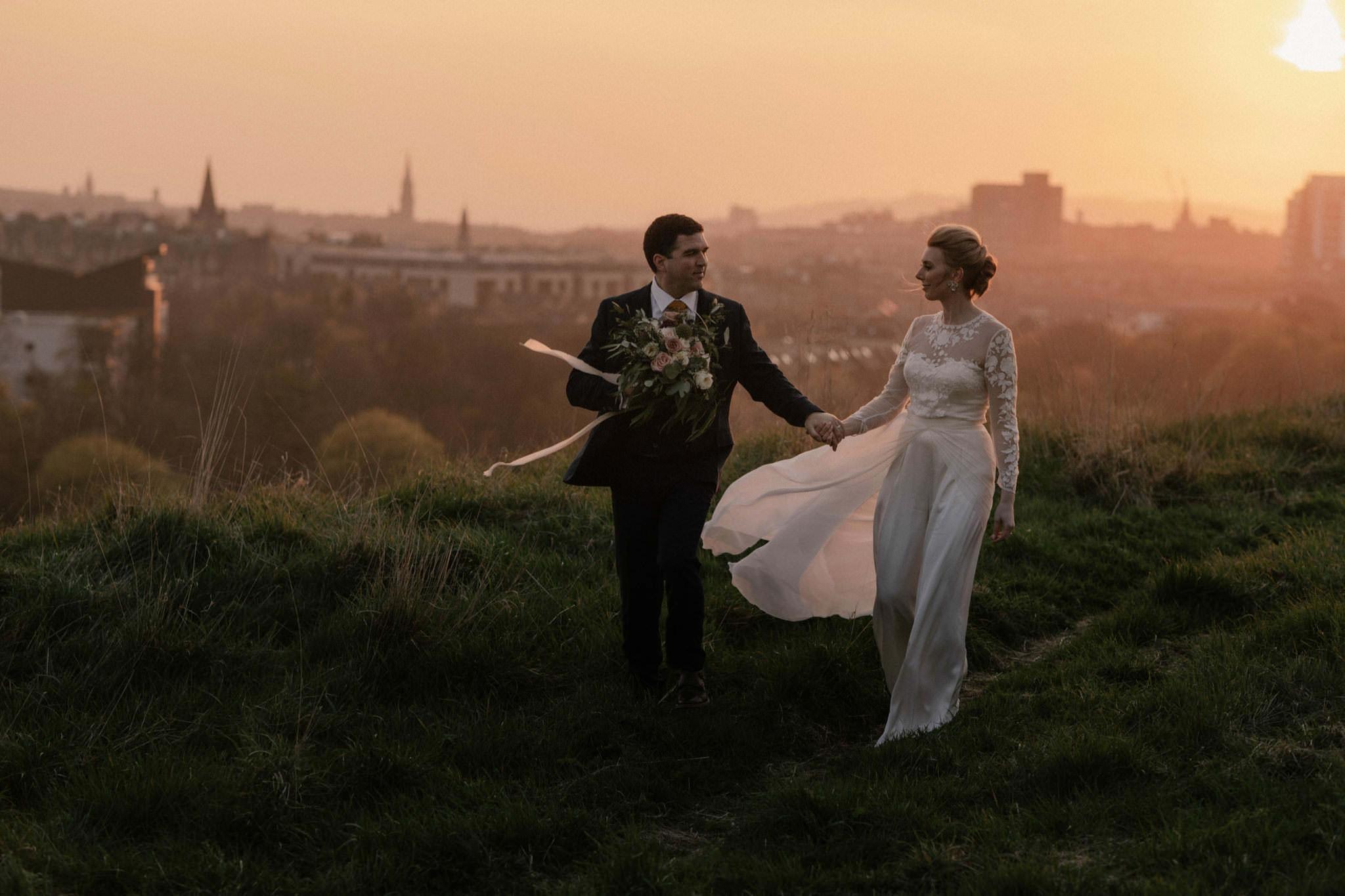 Edinburgh wedding couple walk on Arthur's seat at sunset