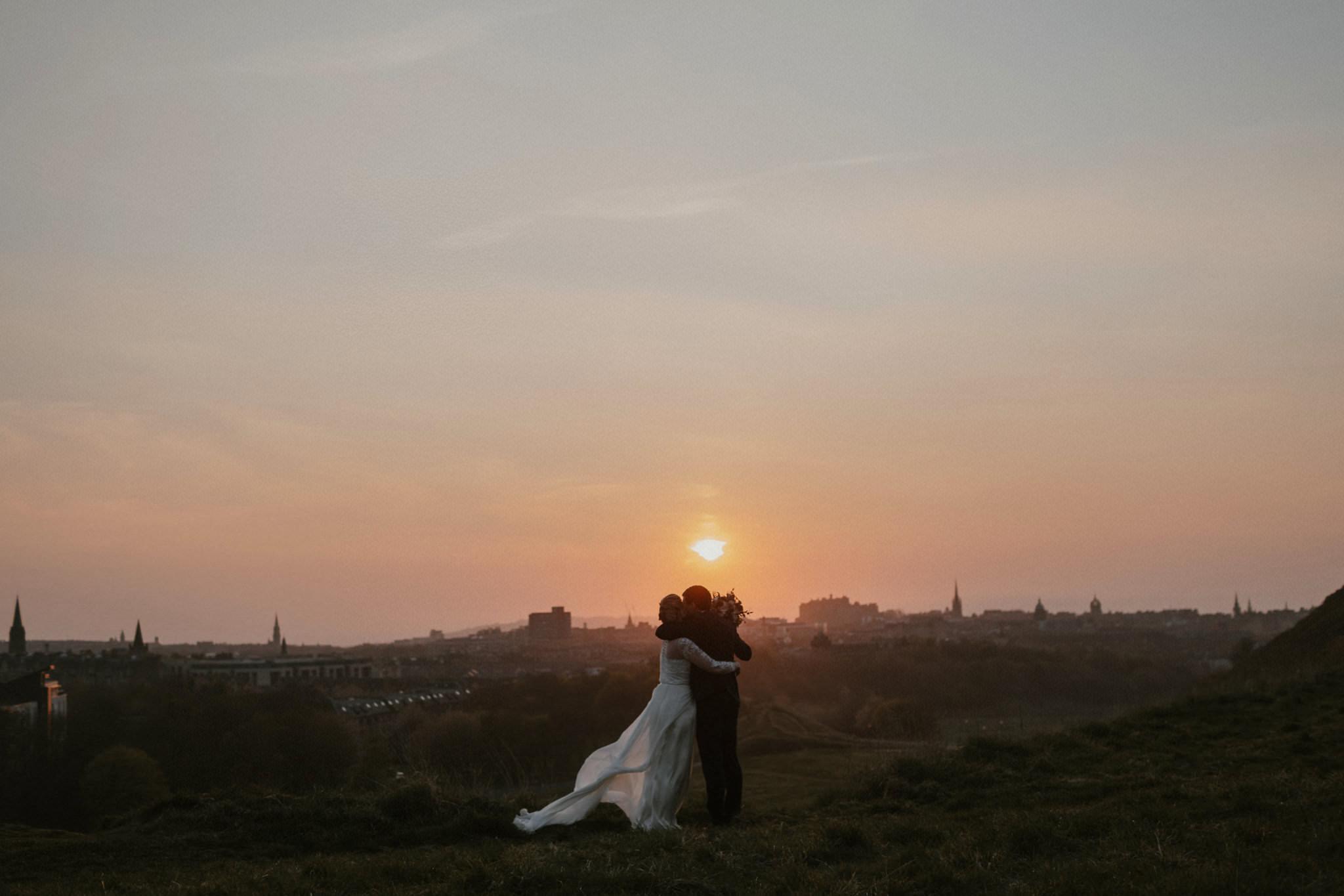 Edinburgh wedding photography couple embrace on Arthur's seat at sunset