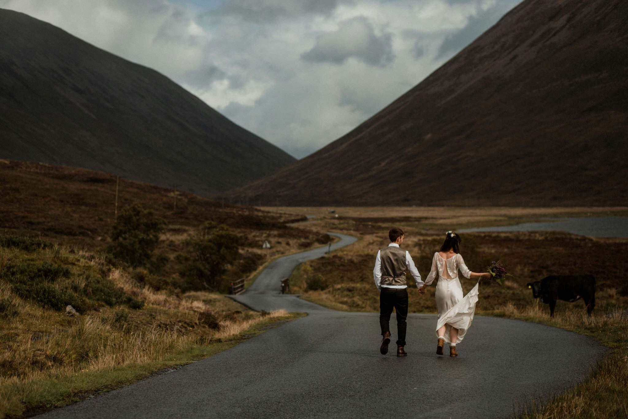 Newlyweds walk down a road in the Isle of Skye