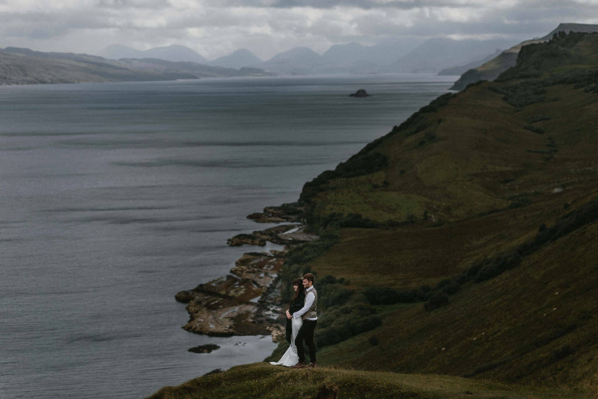 A couple stare out towards Raasay on the Isle of Skye