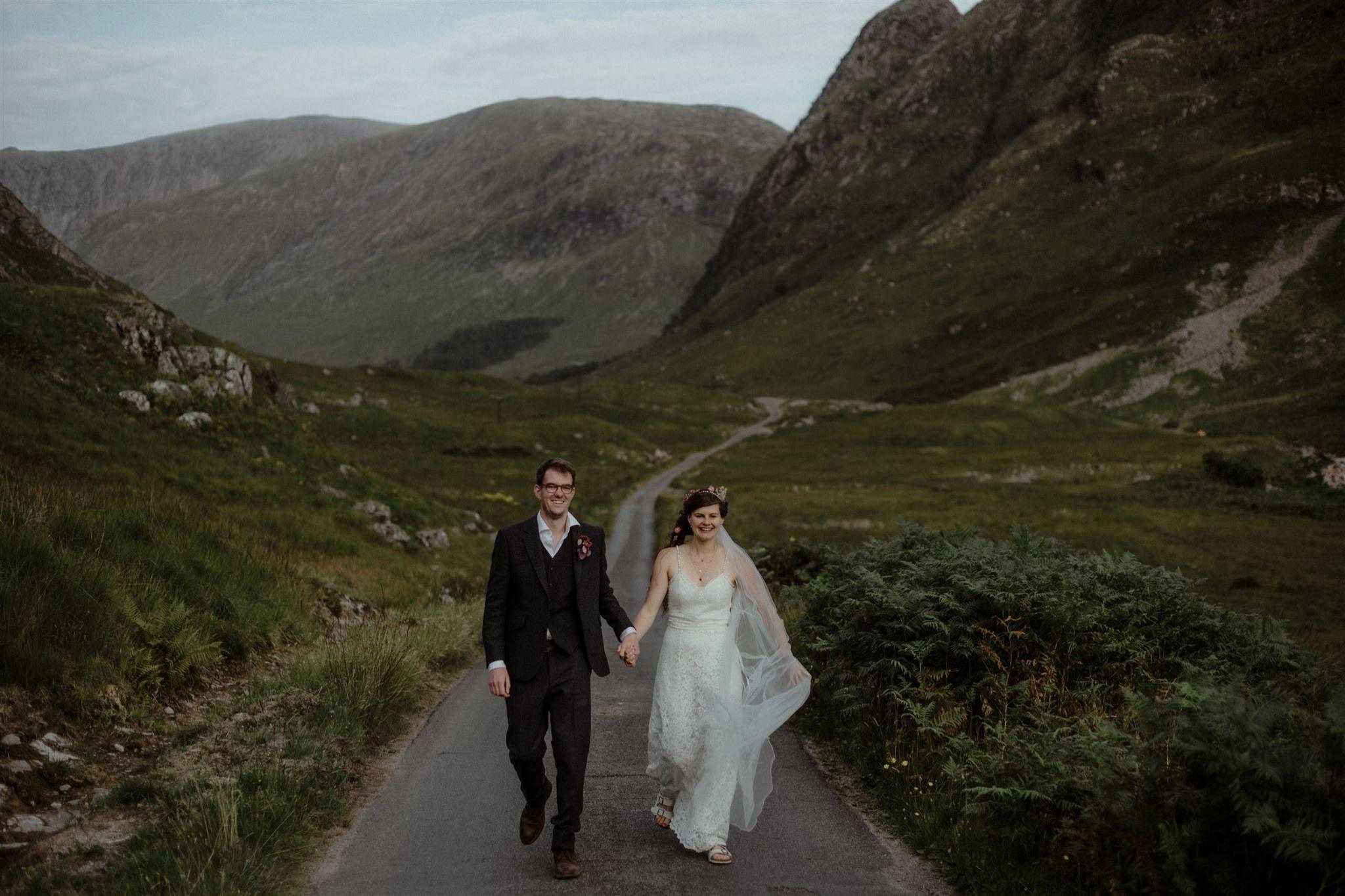 Elopement wedding couple walking down a road in Glen Etive Glencoe