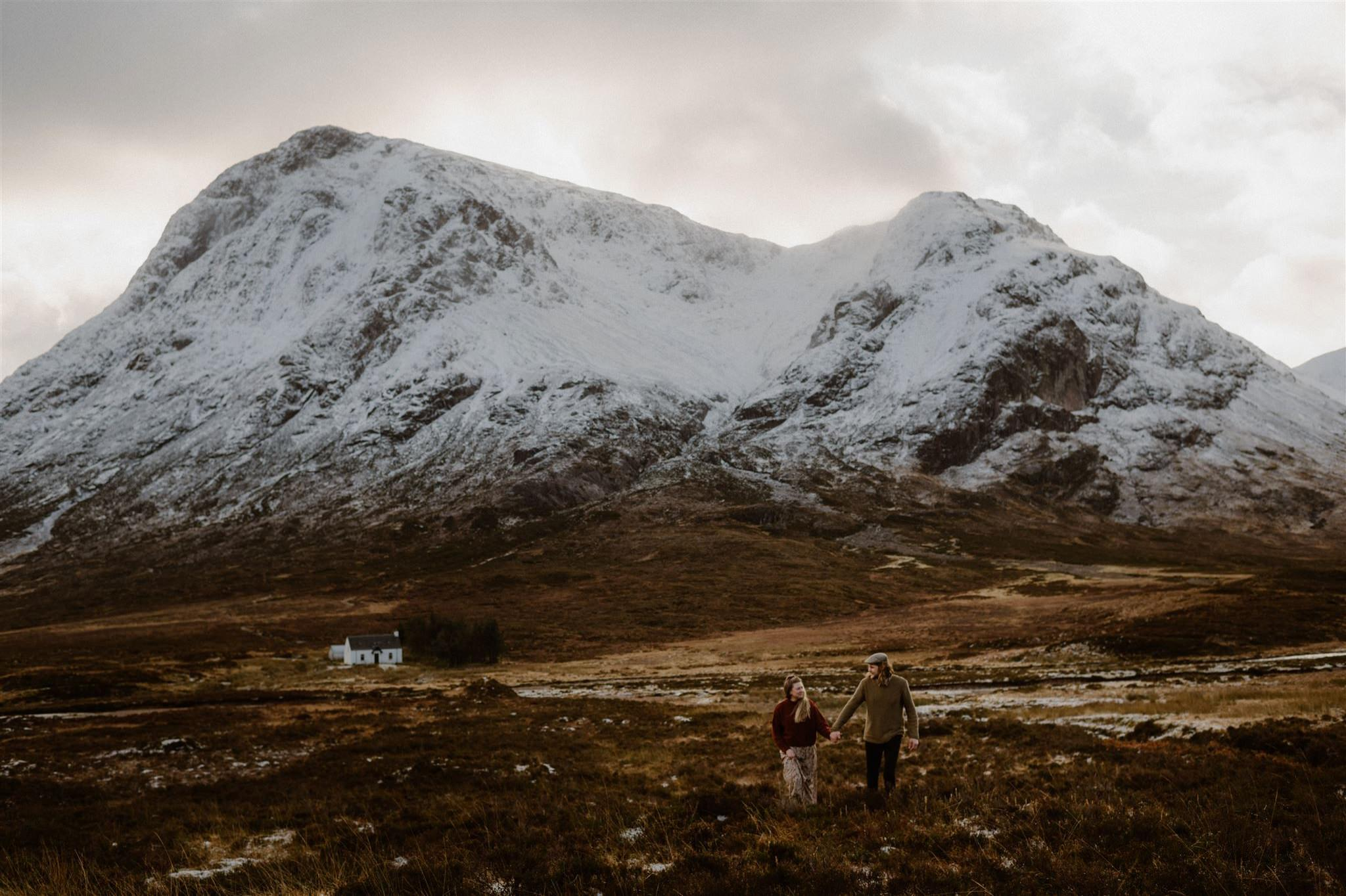Elopement wedding couple holding hands in front of a mountain backdrop in Glencoe Scottish Highlands