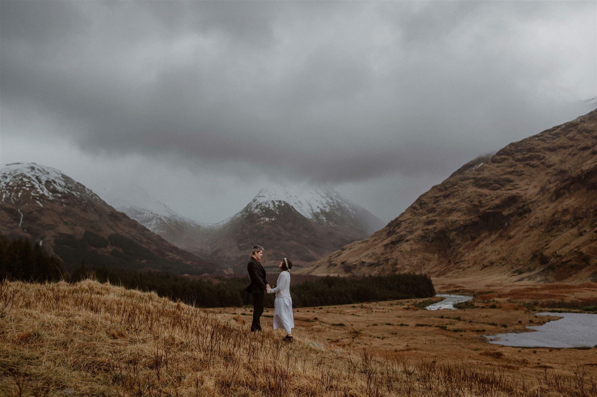 Elopement wedding ceremony couple holding hands in Glen Etive Glencoe in Scotland