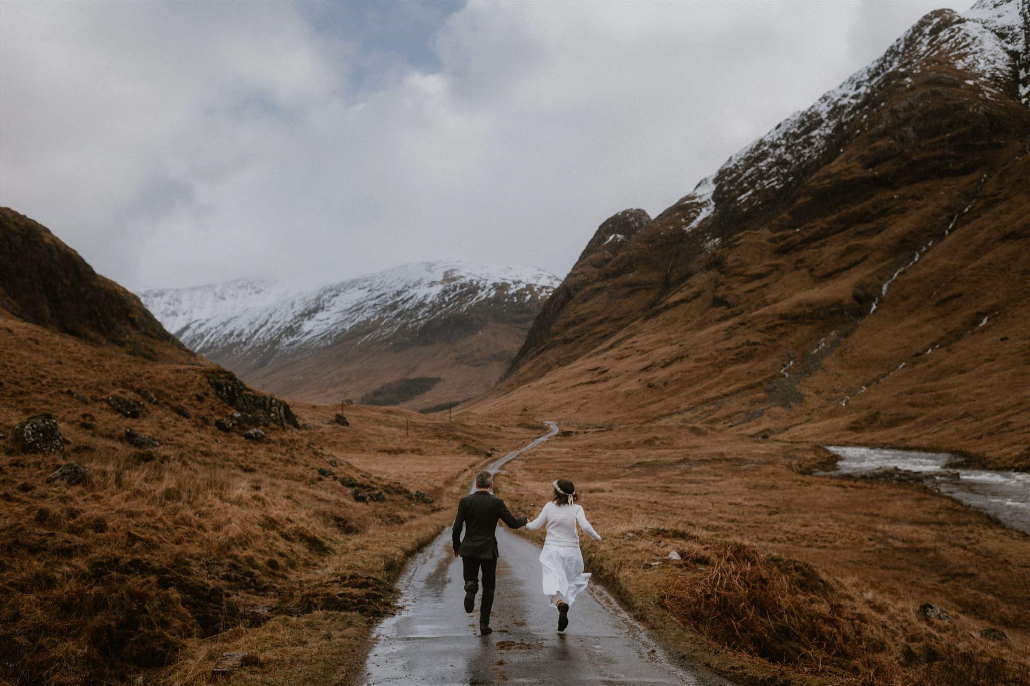 Elopement wedding ceremony couple holding hands running down the road in Glen Etive Glencoe in Scotland