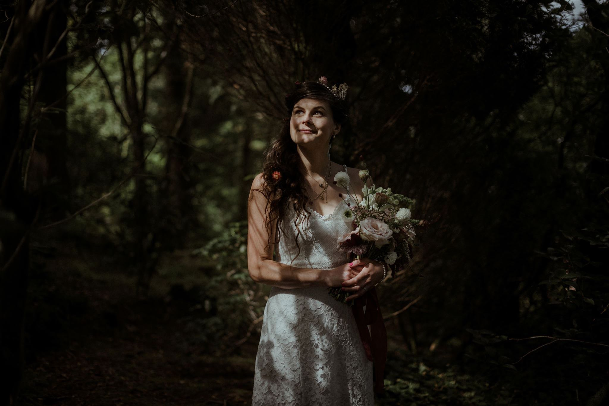Bride holding a flower bouquet in woodland