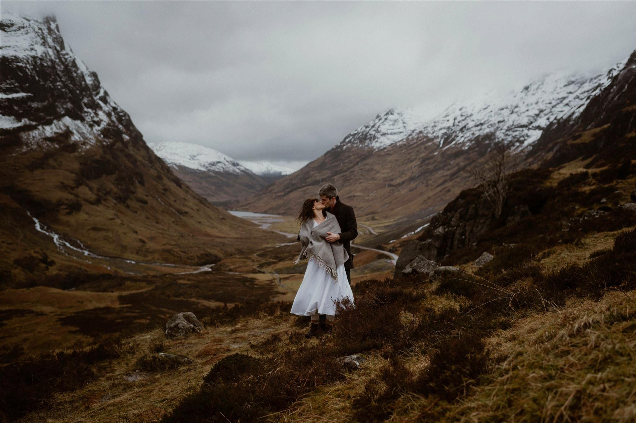Couple kissing with a panoramic Glencoe valley backdrop