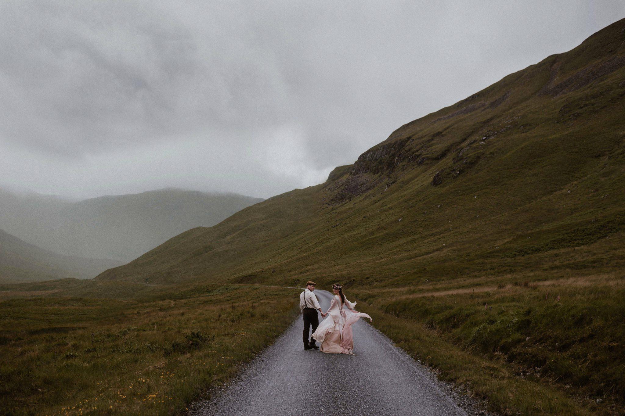 Bride and groom holding hands walking down a road in the Scottish Highlands