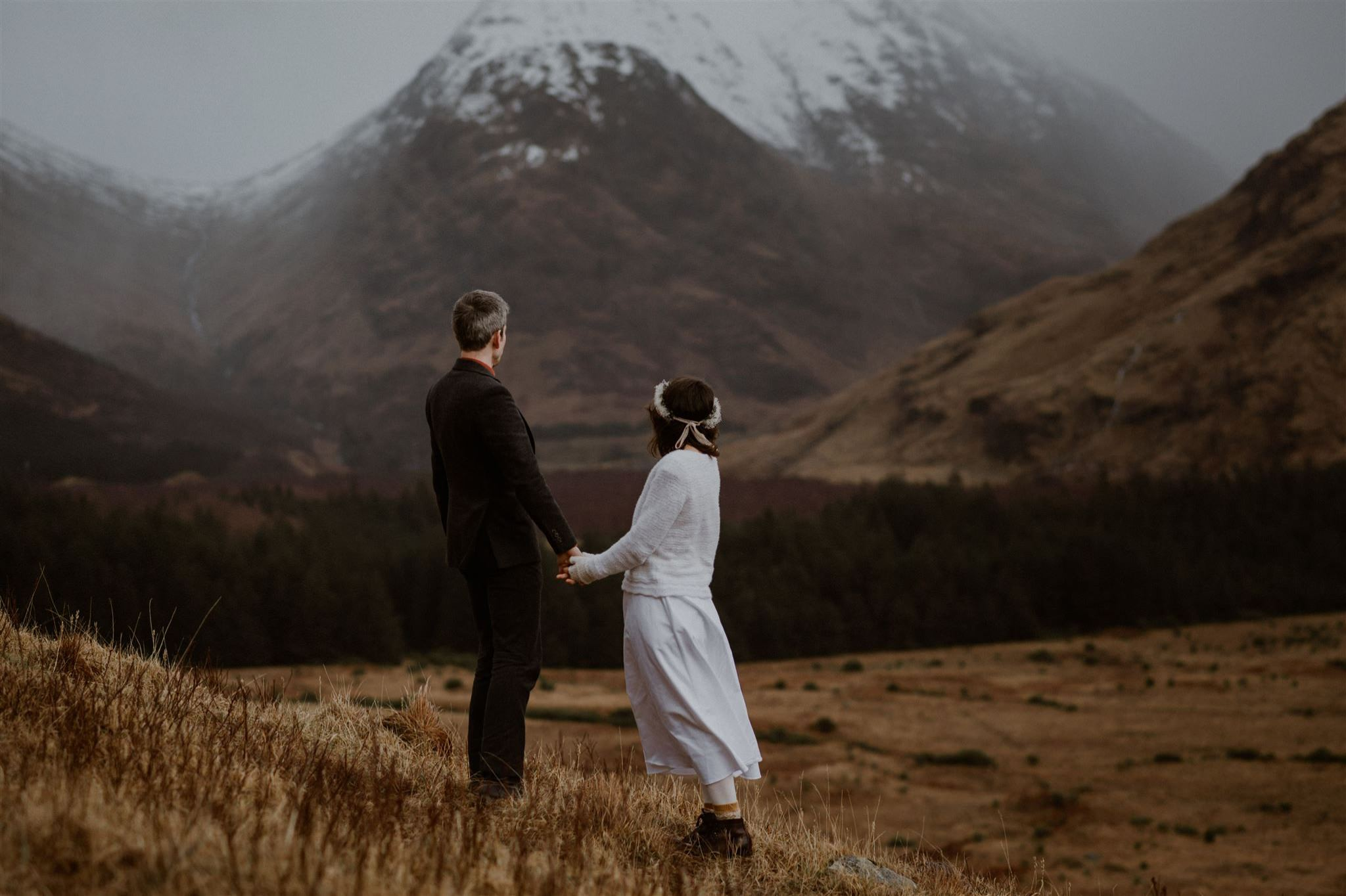 Bride and groom holding hands during their Glencoe elopement wedding in Scotland
