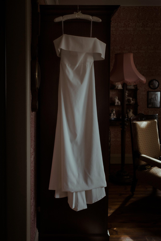 Wedding dress hangs in a bedroom at The Fife Arms Braemar