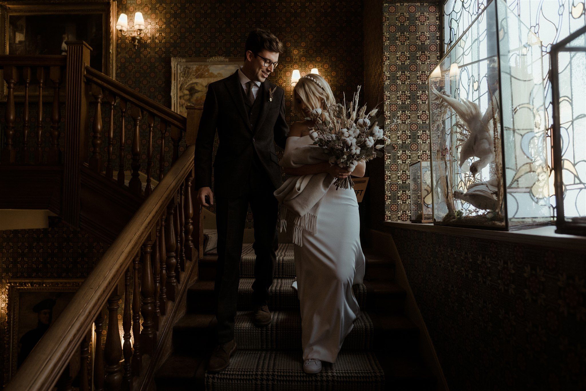 Bride and groom on a staircase at The Fife Arms in Braemar