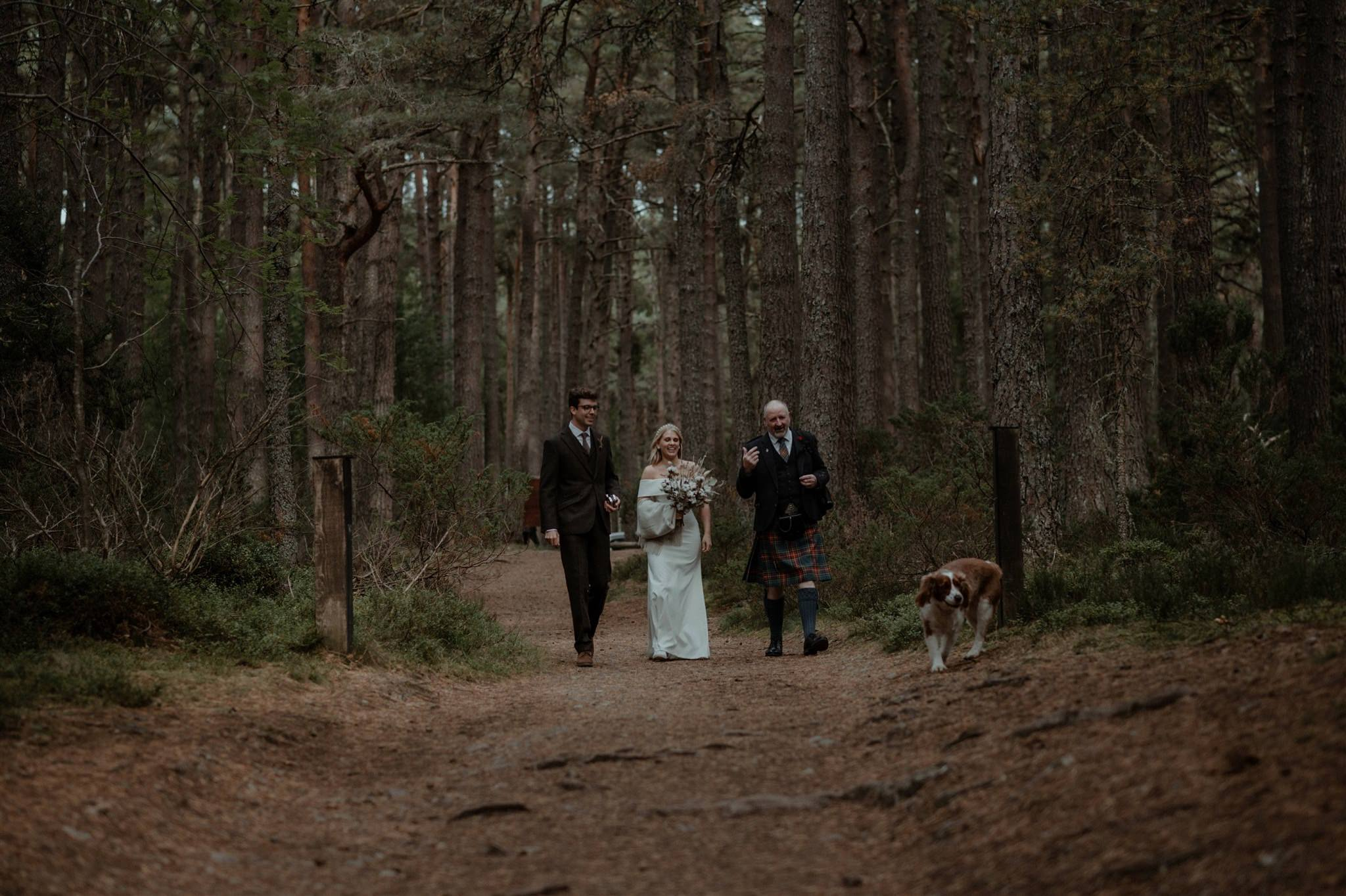 Bride and groom with Humanist celebrant in the forest at Loch Garten
