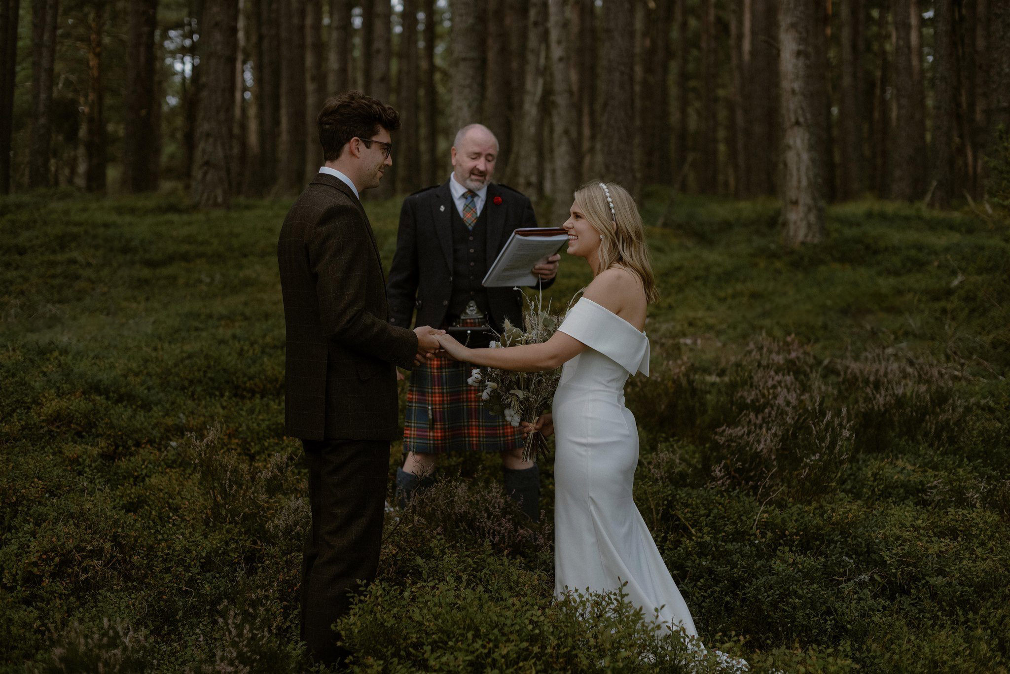 Bride and groom exchange vows at woodland elopement ceremony at Loch Garten