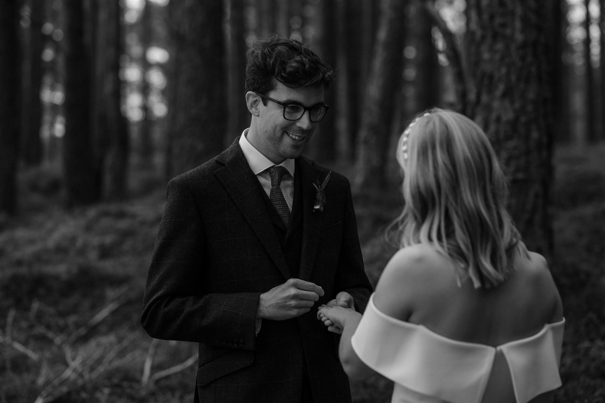 Groom holding wedding ring at a Cairngorms elopement