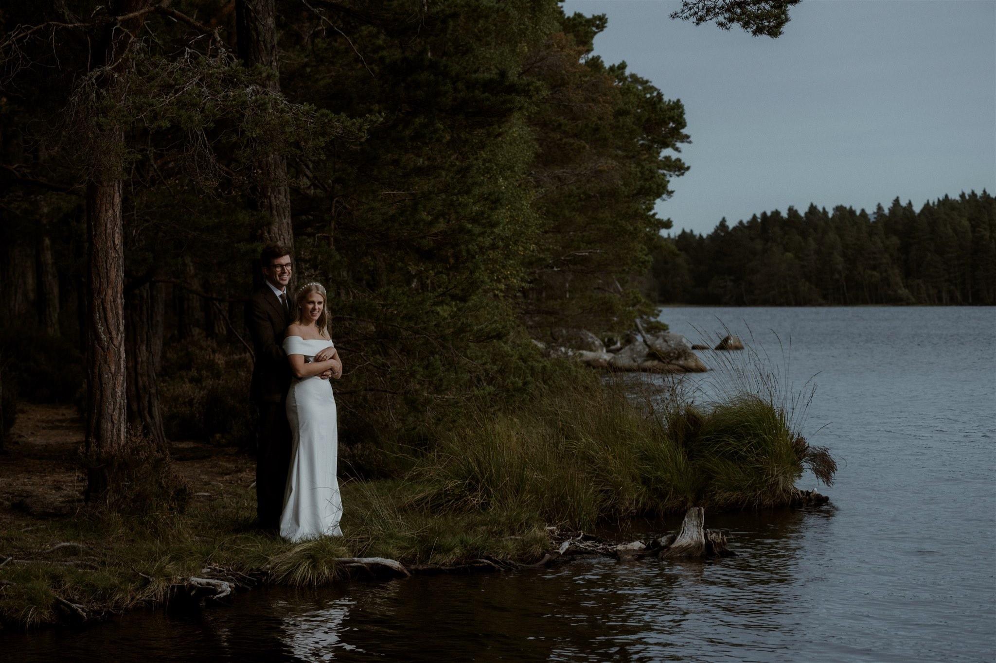 Bride and groom standing by Loch Garten