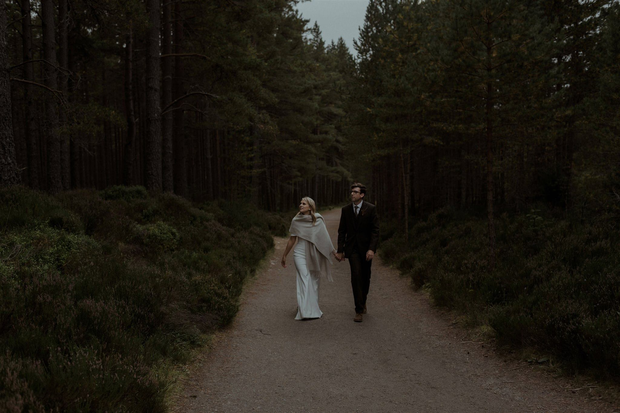 Bride and groom walk through the forest near Glenmore Lodge in the Cairngorms
