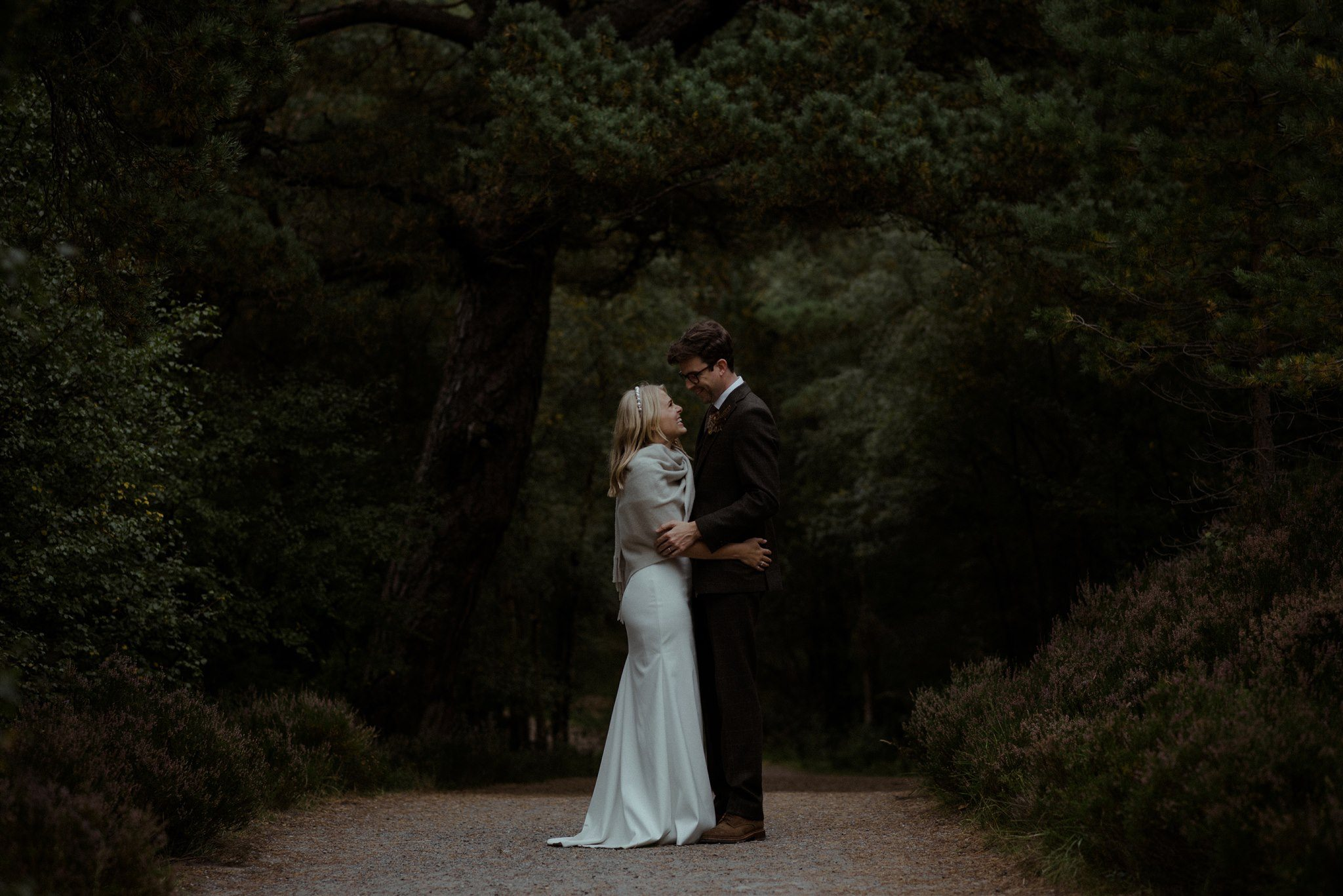 Bride and groom embrace under trees in Glen More in Cairngorms