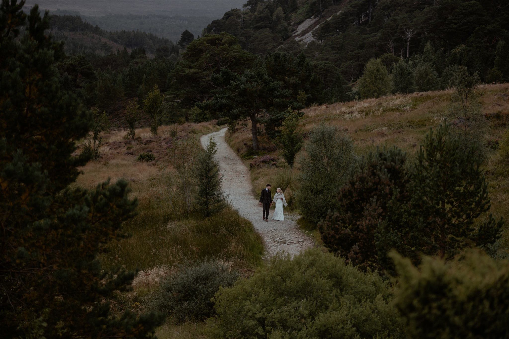 Bride and groom walking towards Ryvoan Lodge in Glen More in the Cairngorms