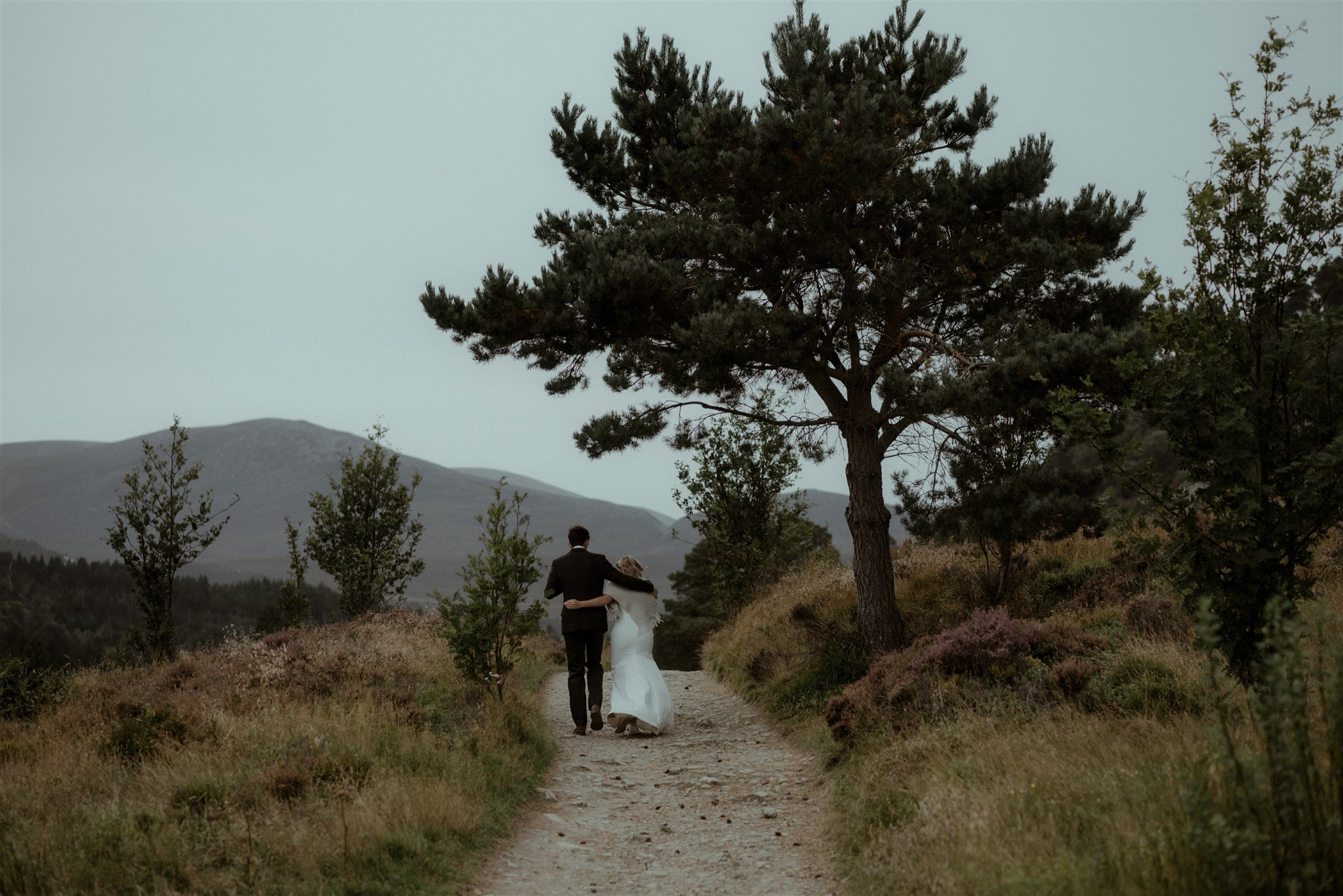 Bride and groom walking on a path through Glen More in the Cairngorms of Scotland
