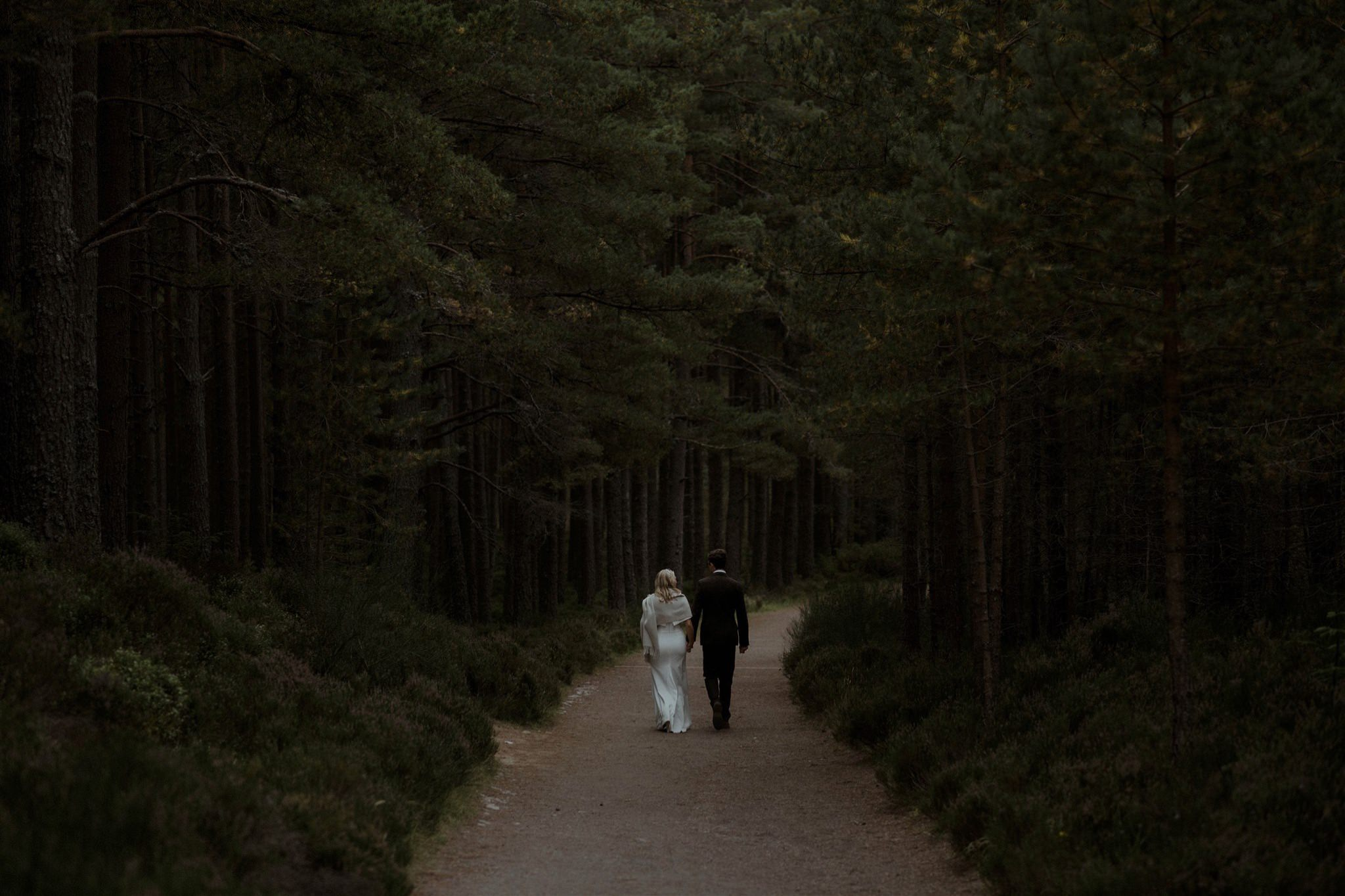 Bride and groom walk along a path through Scottish woodland