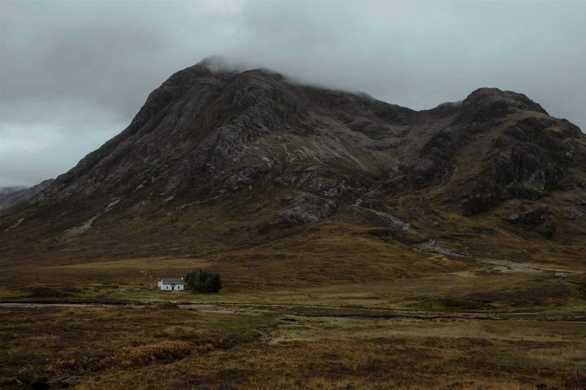 Cottage with mountains in the background in Glencoe, Scotland