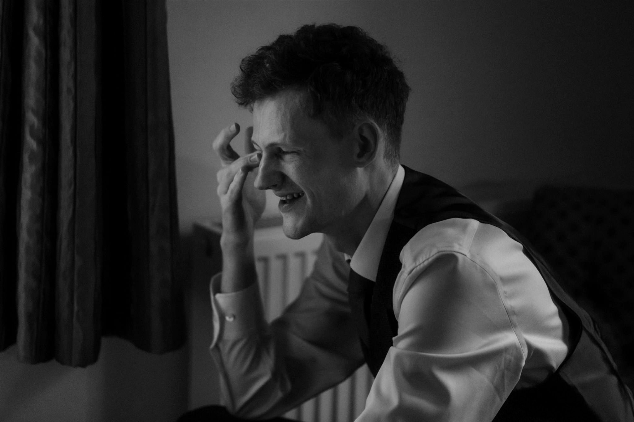Tearful groom reads cards during an elopement in Glencoe, Scotland