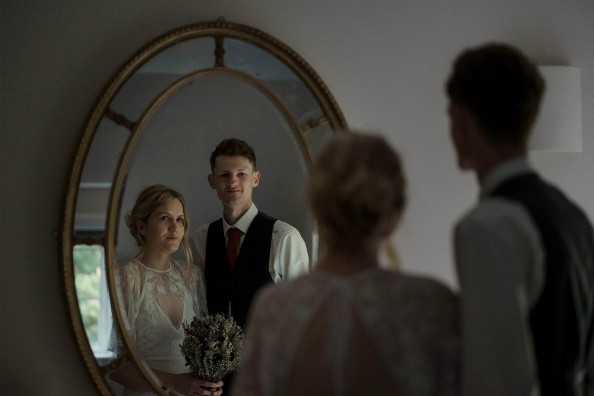 Bride and groom looking in mirror during their wedding for two in Scotland