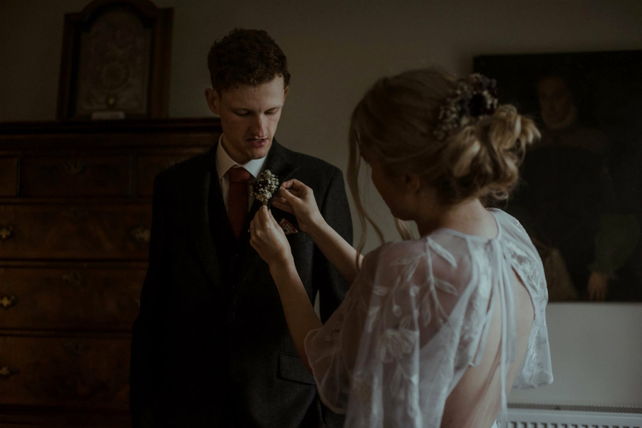 Bride pins on buttonhole during a Glencoe elopement wedding day