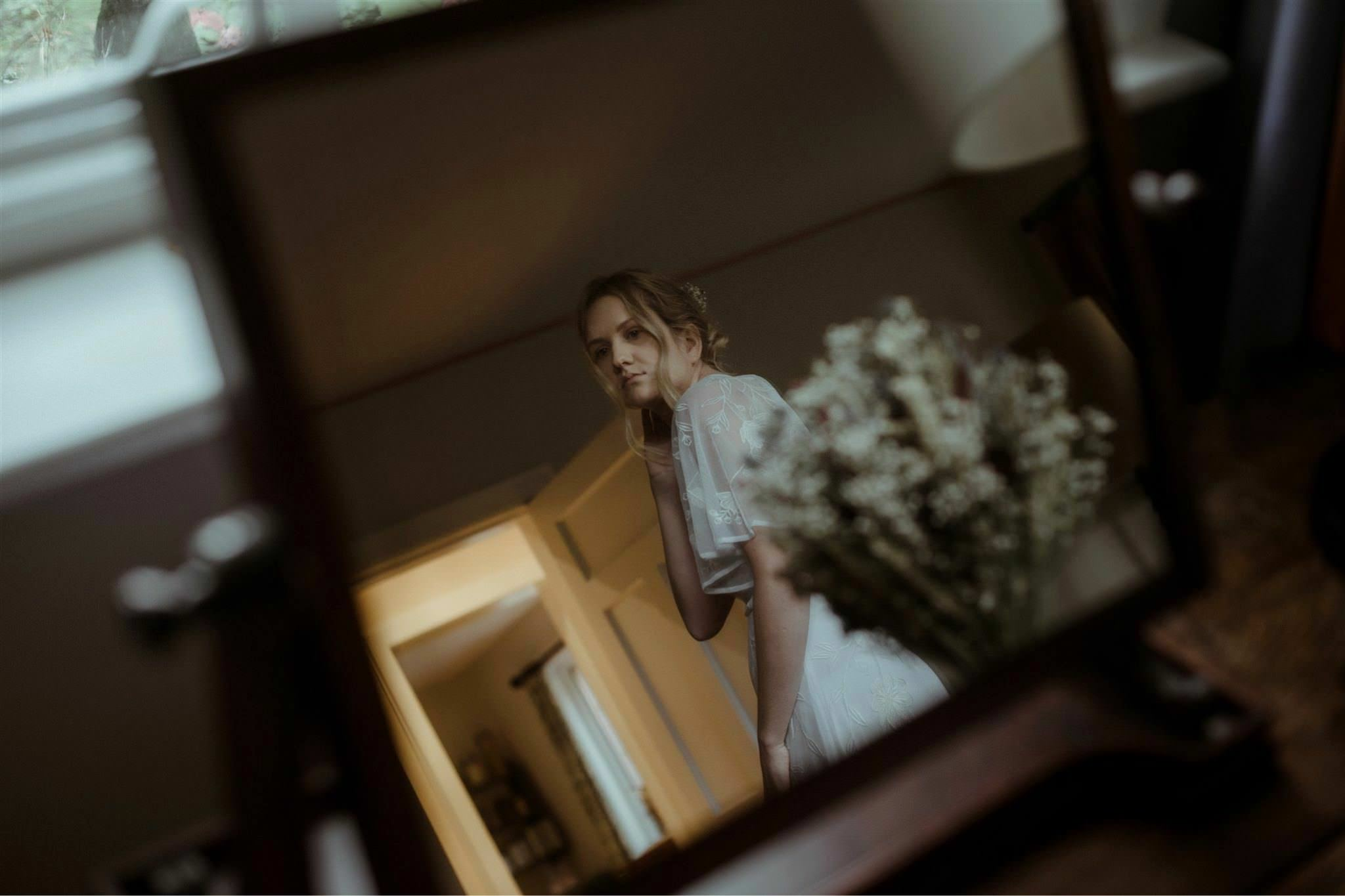 Bride looks at herself in the mirror during a Glencoe elopement wedding