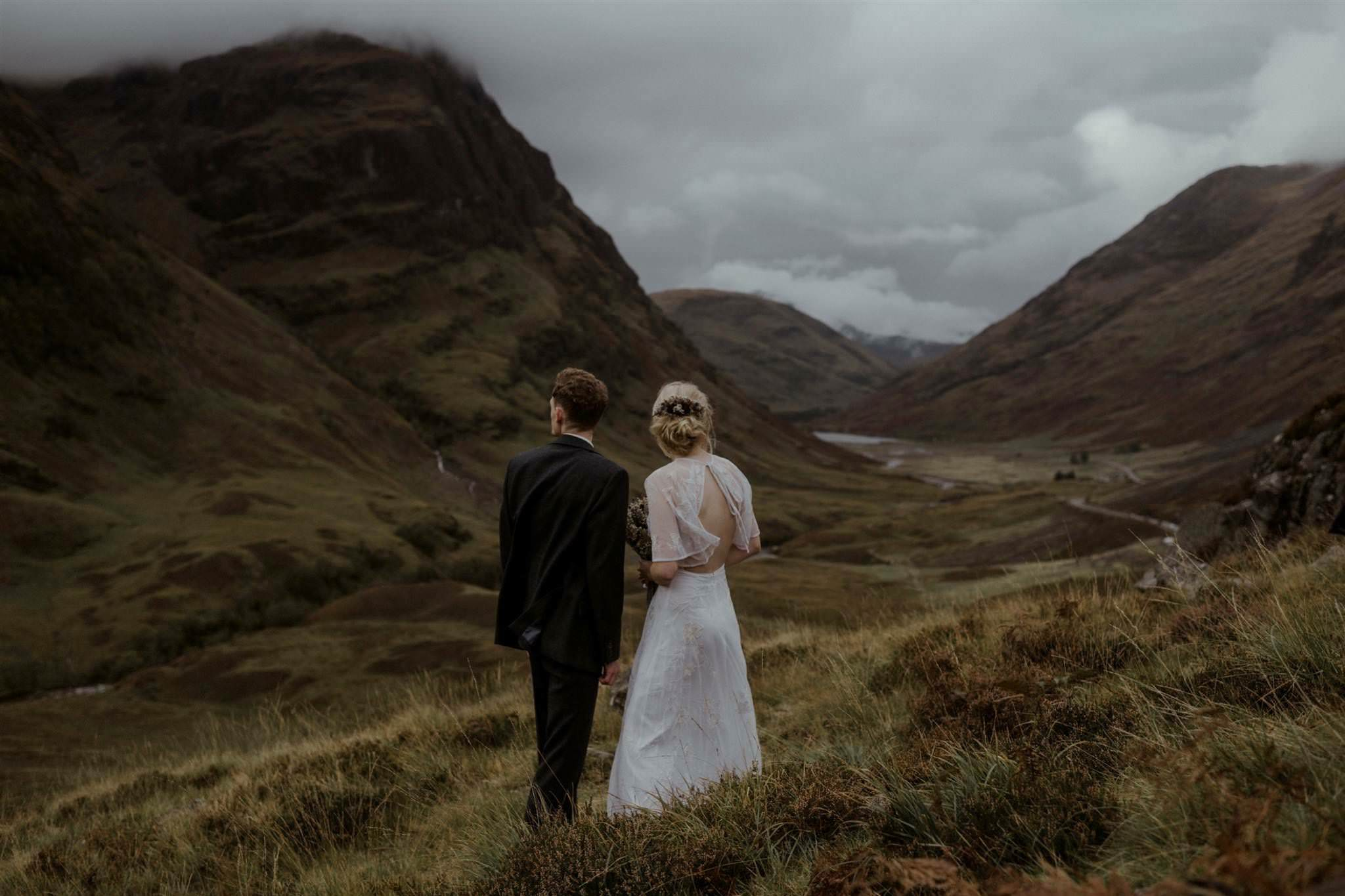 Bride and groom look at mountains during their Glencoe elopement in Scotland