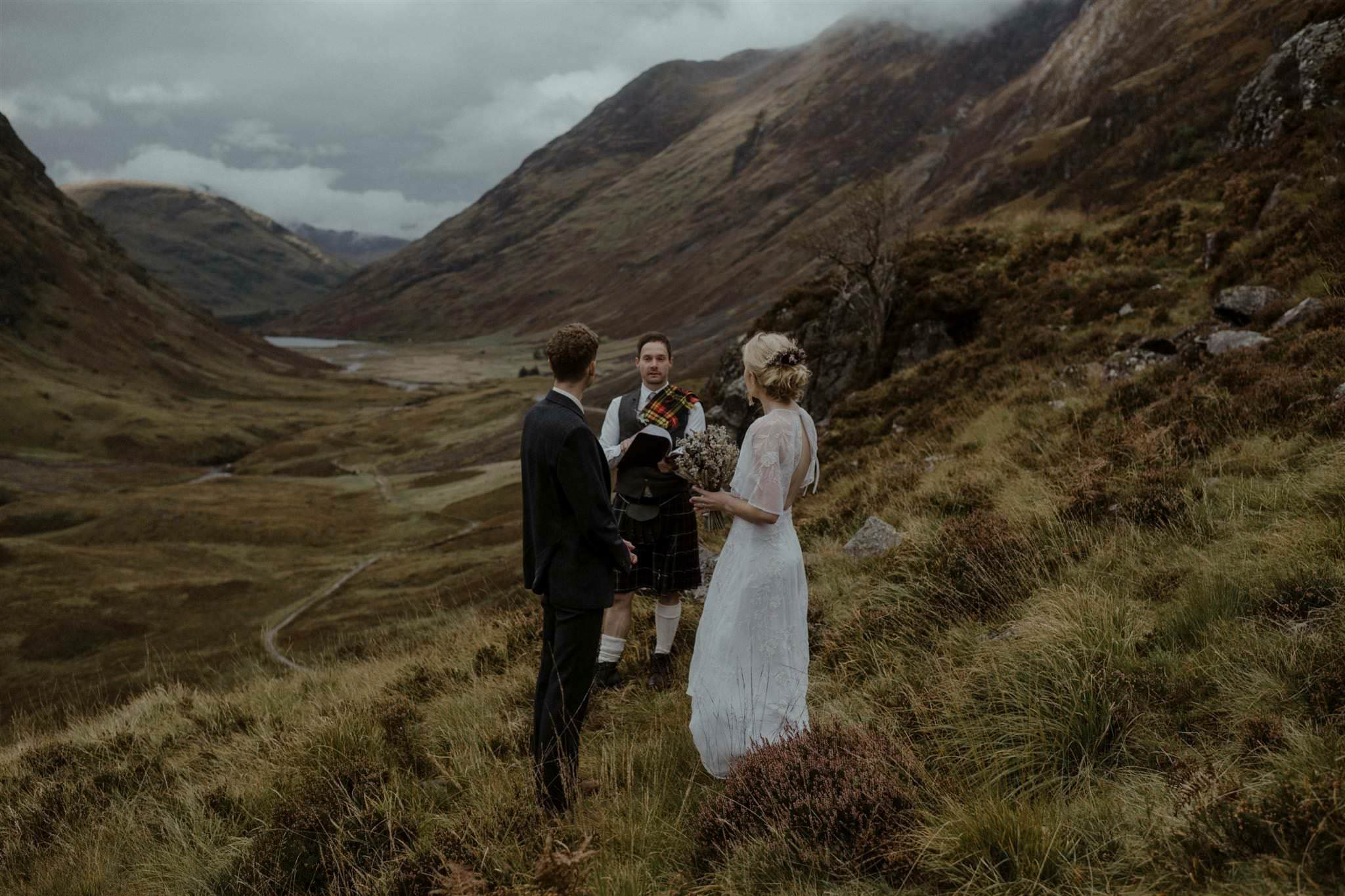 Bride, groom and humanist celebrant during an outdoor elopement wedding ceremony in Glencoe, Scottish Highlands