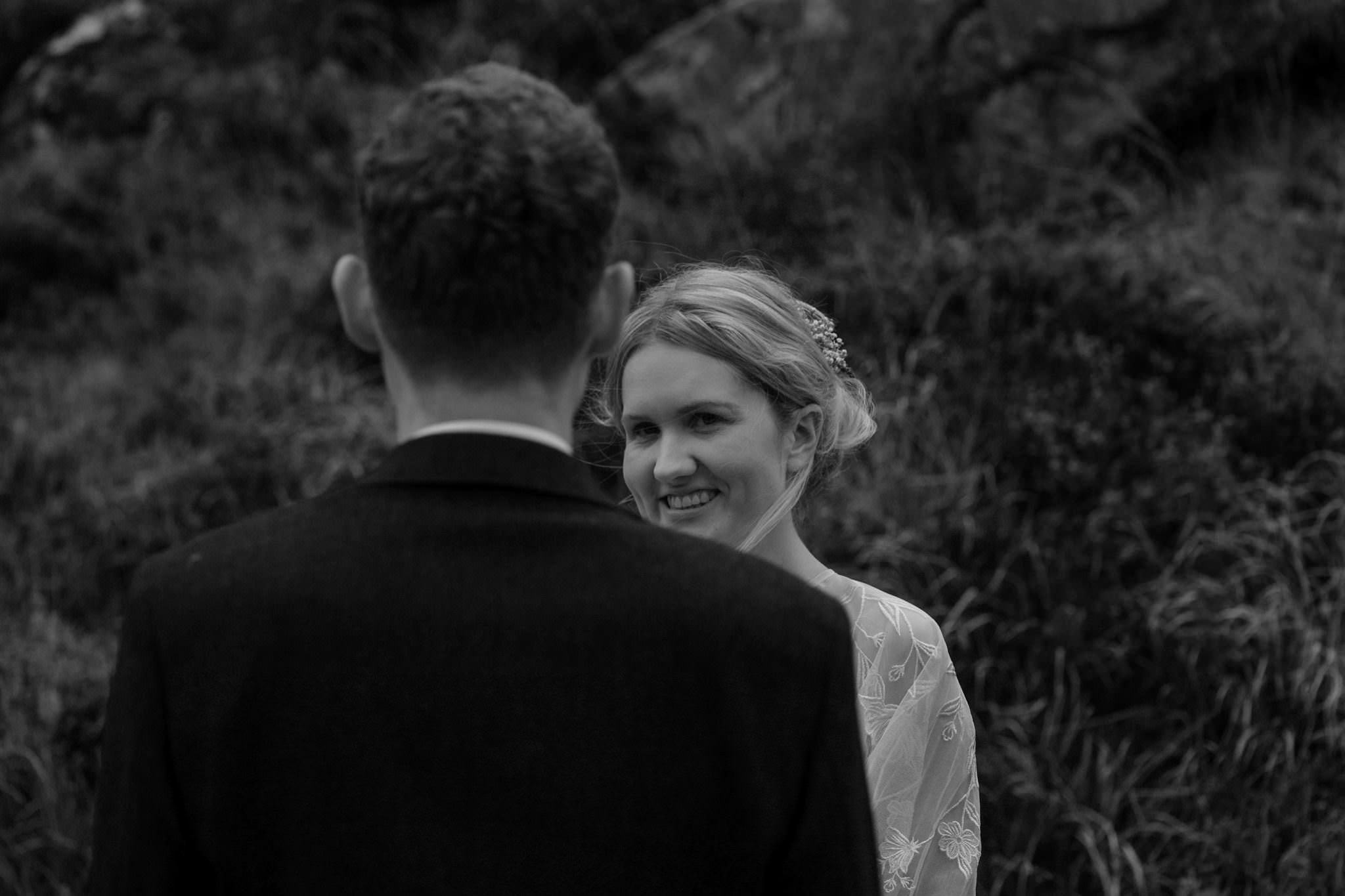 Bride looks at groom during a Glencoe elopement wedding ceremony in Scotland