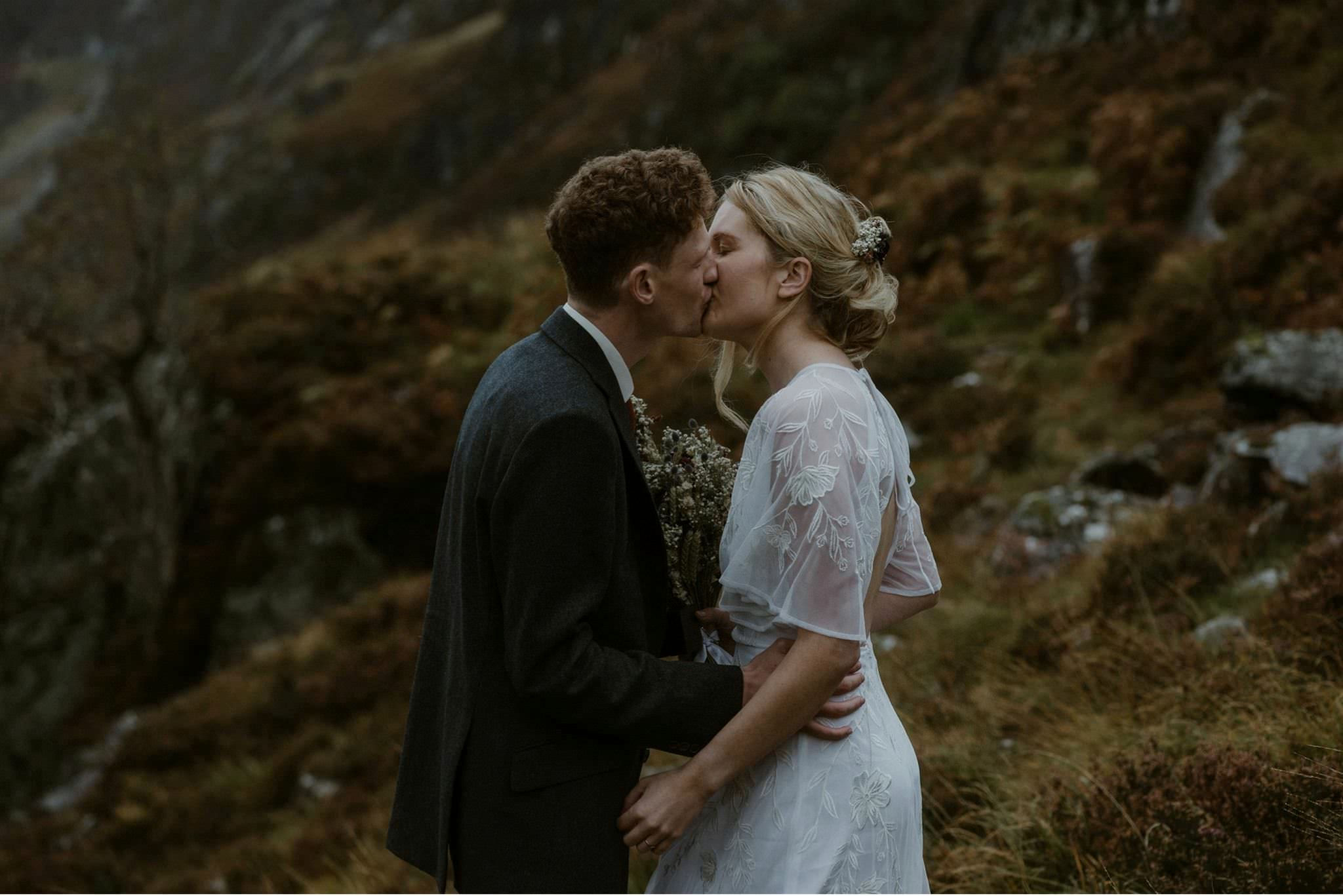 Bride and groom kiss during their wedding for two in Glencoe, Scotland