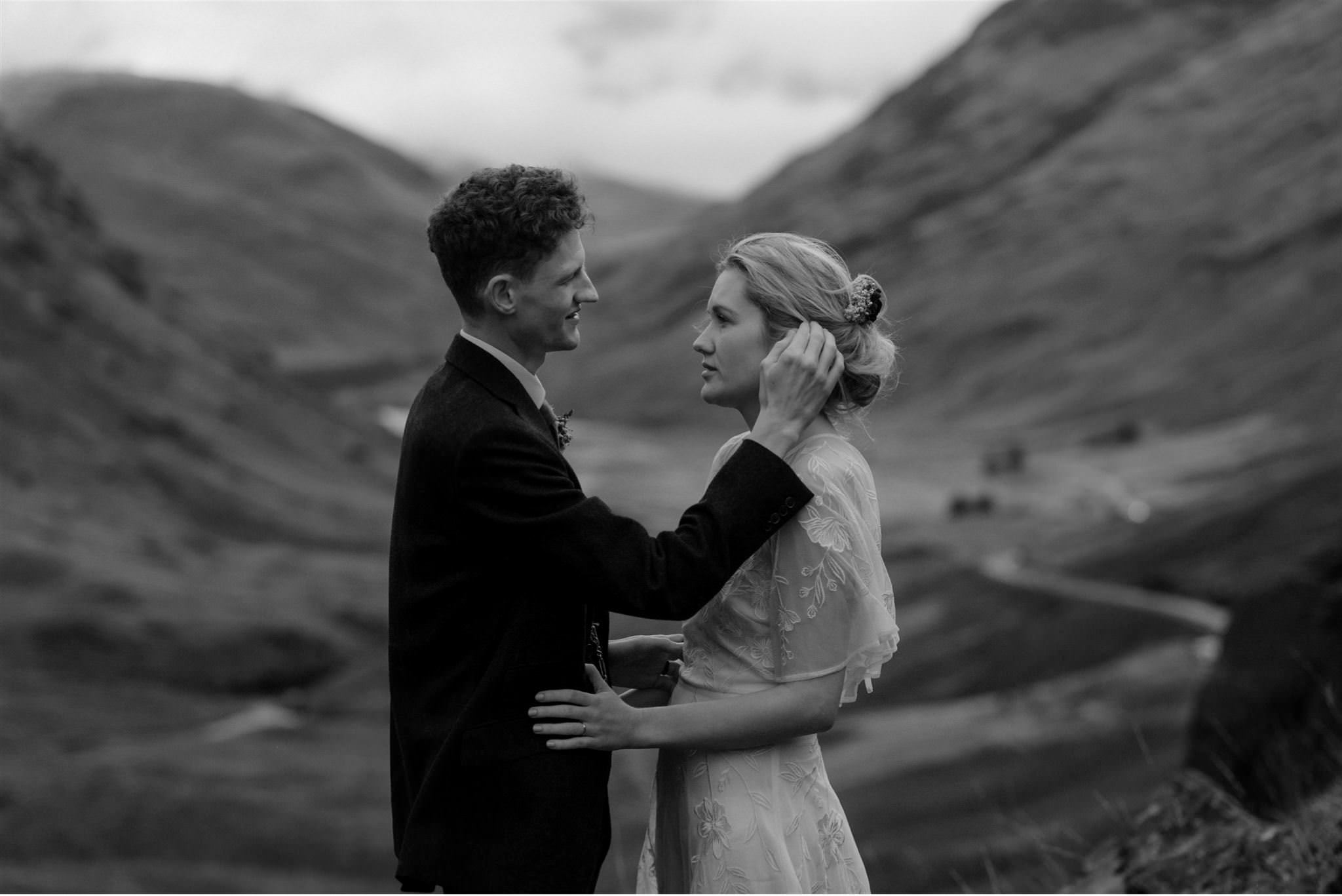 Groom caresses bride during their elopement in Glencoe, Scotland