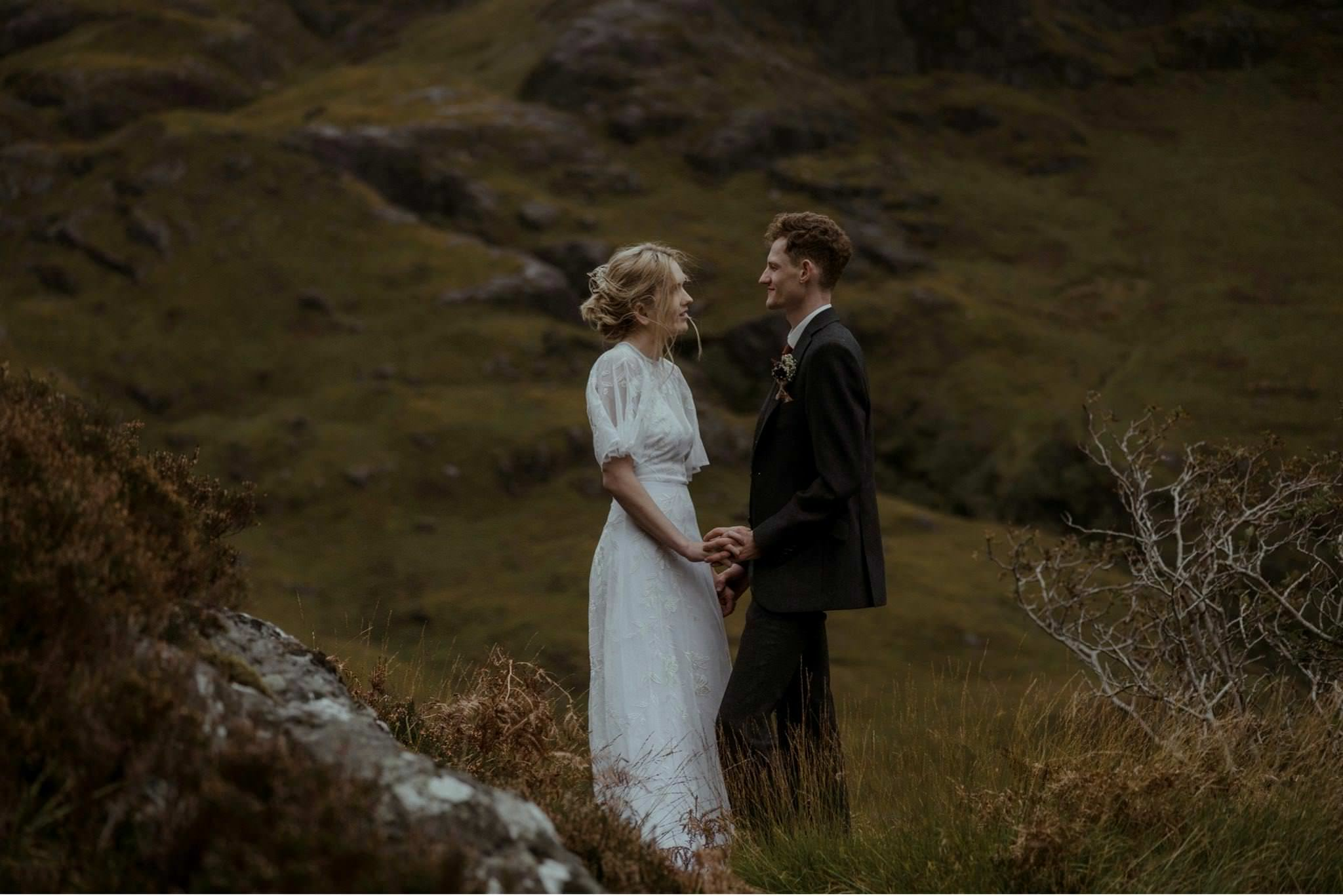 Bride and groom hold hands at their wedding for two in Glencoe Scotland