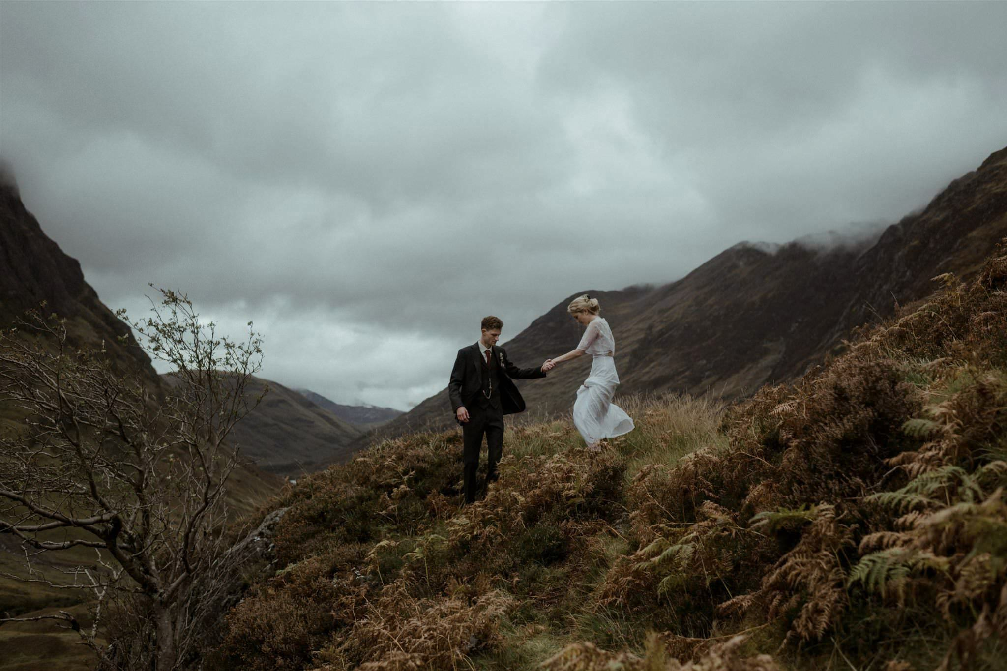 Groom helps bride walk down mountain after their Glencoe elopement wedding ceremony in Scotland