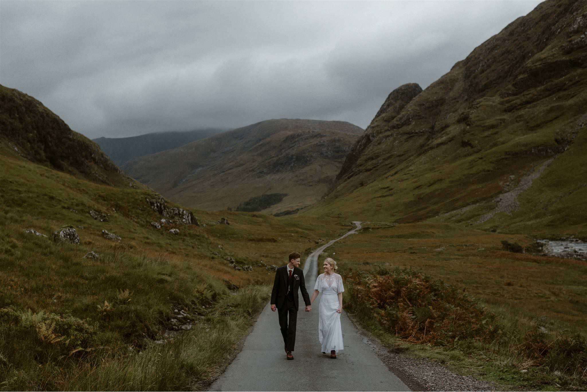 Bride and groom walk down road in Glen Etive after their elopement wedding in Scotland