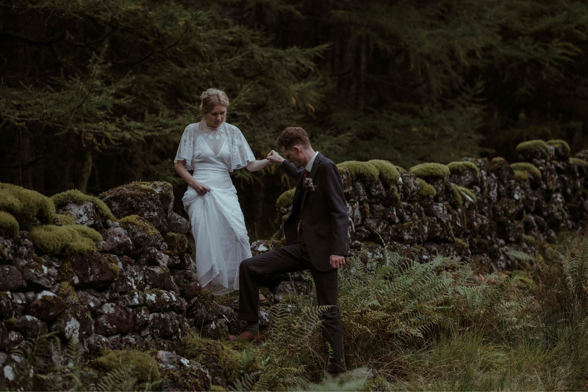 Groom helps bride over a wall in Glen Etive after their Glencoe elopement wedding