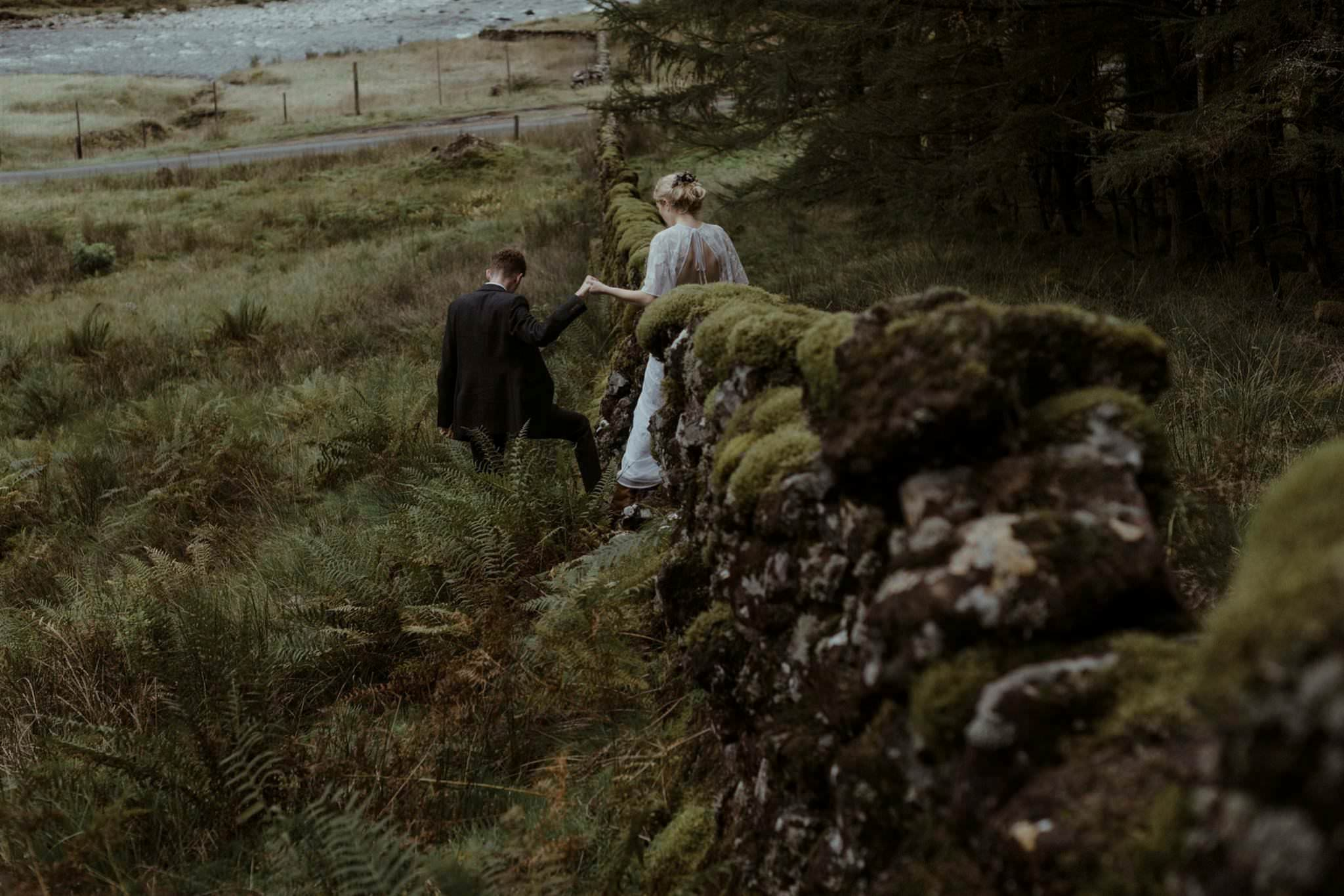 Groom helps bride over a wall in Glen Etive after their wedding for two in Scotland