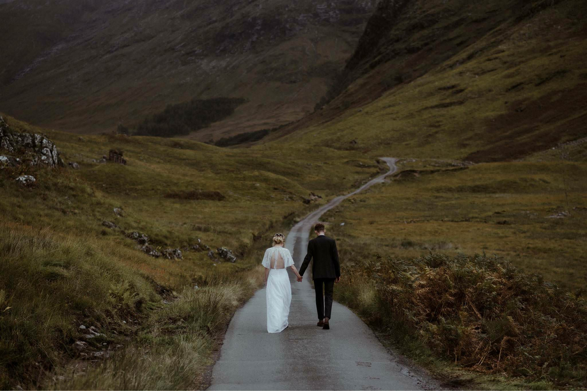 Bride and groom walking up road in Glen Etive after their Glencoe elopement wedding in Scotland